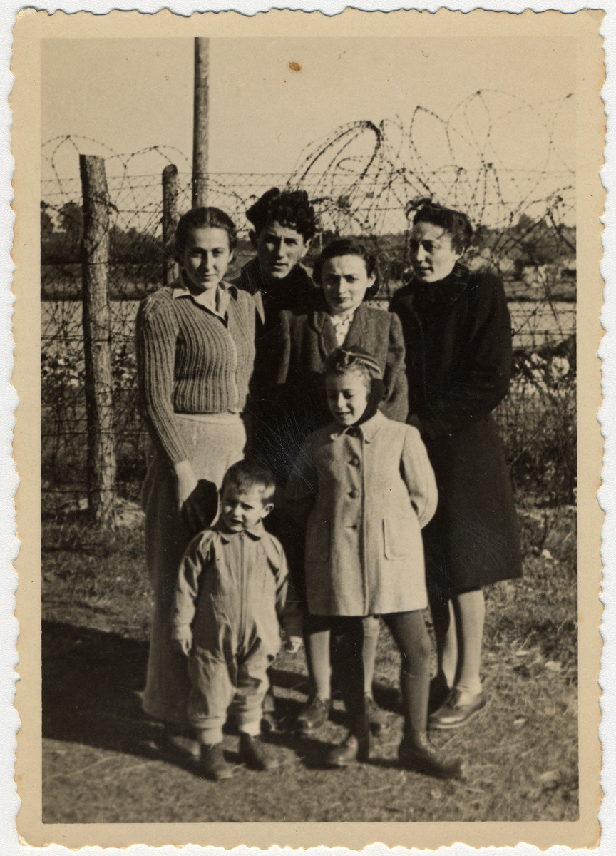 Jewish DPs pose together in front of a barbed wire fence.    Pictured on the left are Giza and Reuwen Wiernik and their son Alexander.