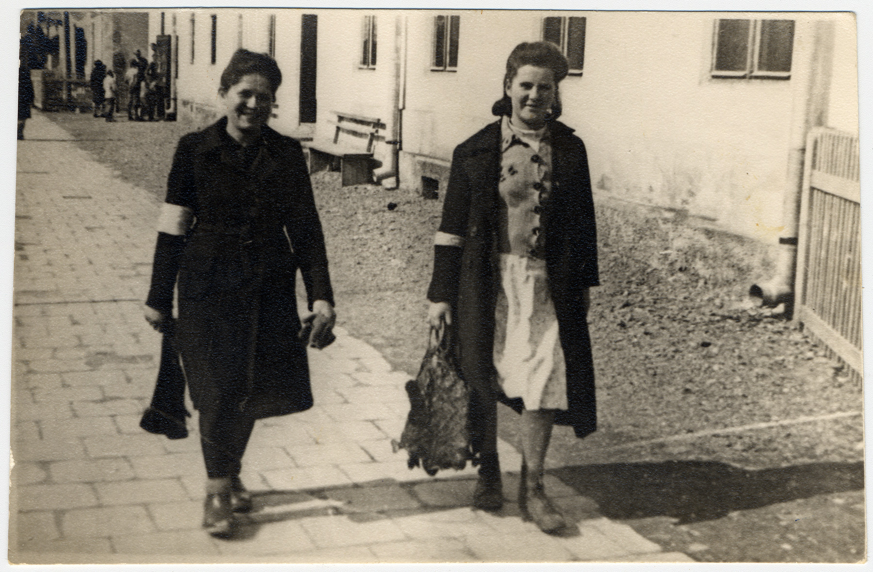 Two young women wearing armbands walk down a street near the town square in the Bolechow ghetto.   Pictured, on the left, is the donor's cousin, Pepcia Diamand, murdered during an Aktion in March 1943, with a friend.