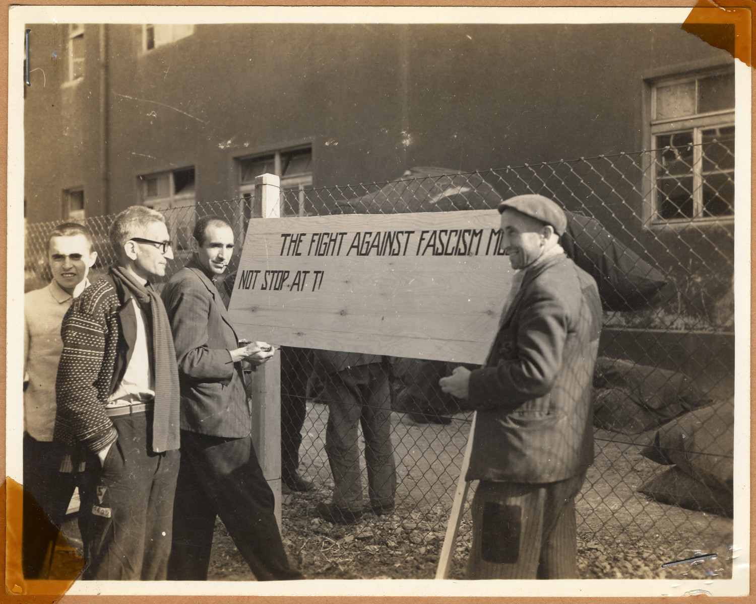 """Survivors in Buchenwald concentration camp stand by a sign that reads """"They fought against Fascism"""".  The lender's handwritten caption reads, """"Russian prisoners happy in the knowledge that soon the Red Army and ours would join and a pathway would be cut through which they would be able to go home."""""""