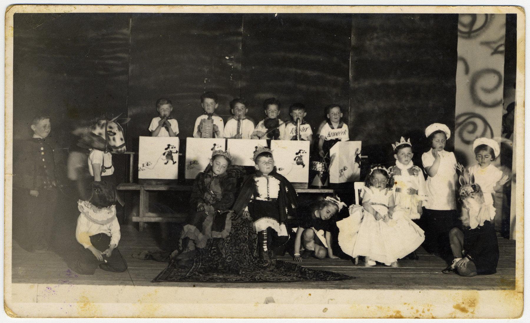 Jewish children put on a school performance at the Novaky forced labor camp.    The donor Mira Menzer, dressed as a queen, sits in the middle.  A boy, Yossi plays the violin and stands third from right