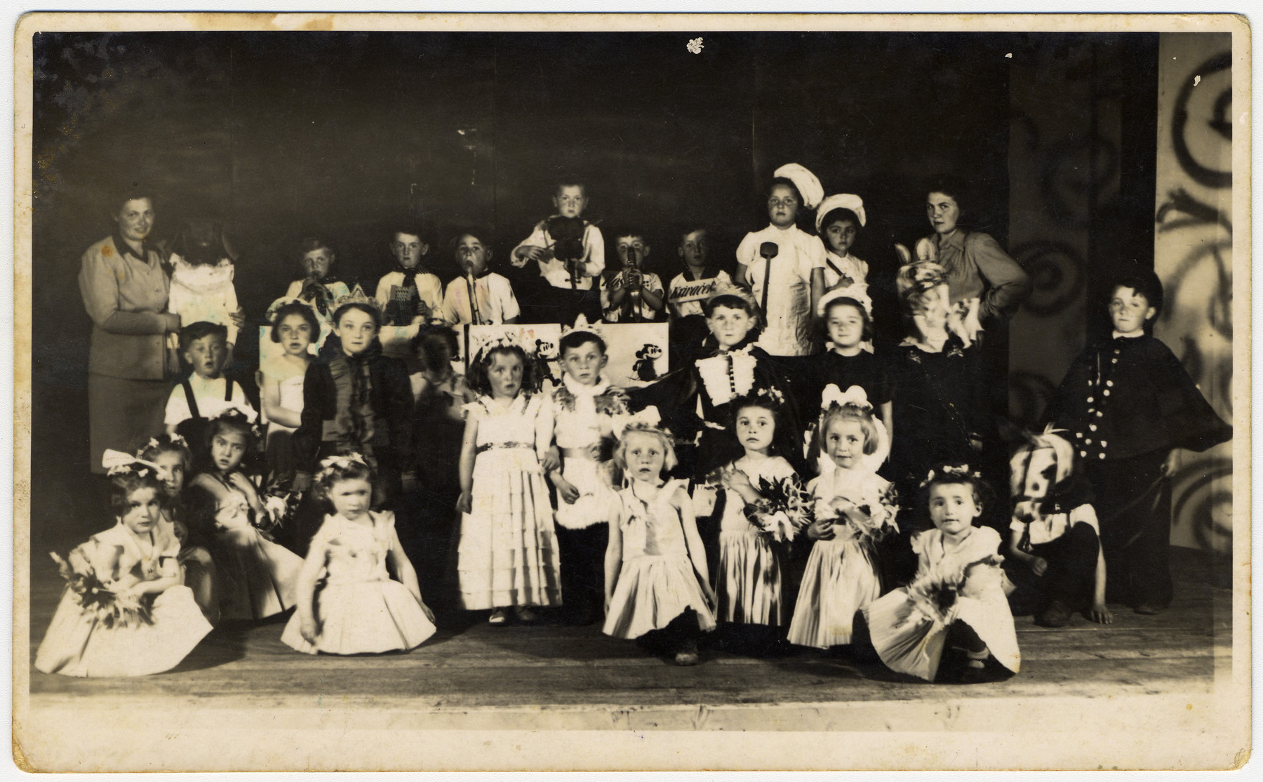 Jewish children put on a school performance at the Novaky forced labor camp.    The donor Mira Menzer, dressed as a queen, is standing third from the left.