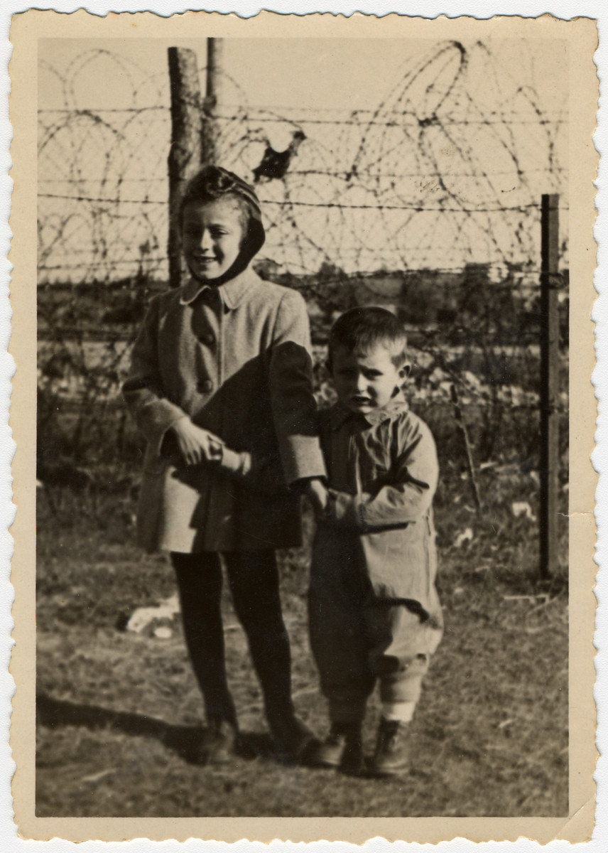 Two children pose in front of a barbed wire fence in the Ziegenhain DP camp.    Pictured are donor's son Alexander with an unidentified girl.