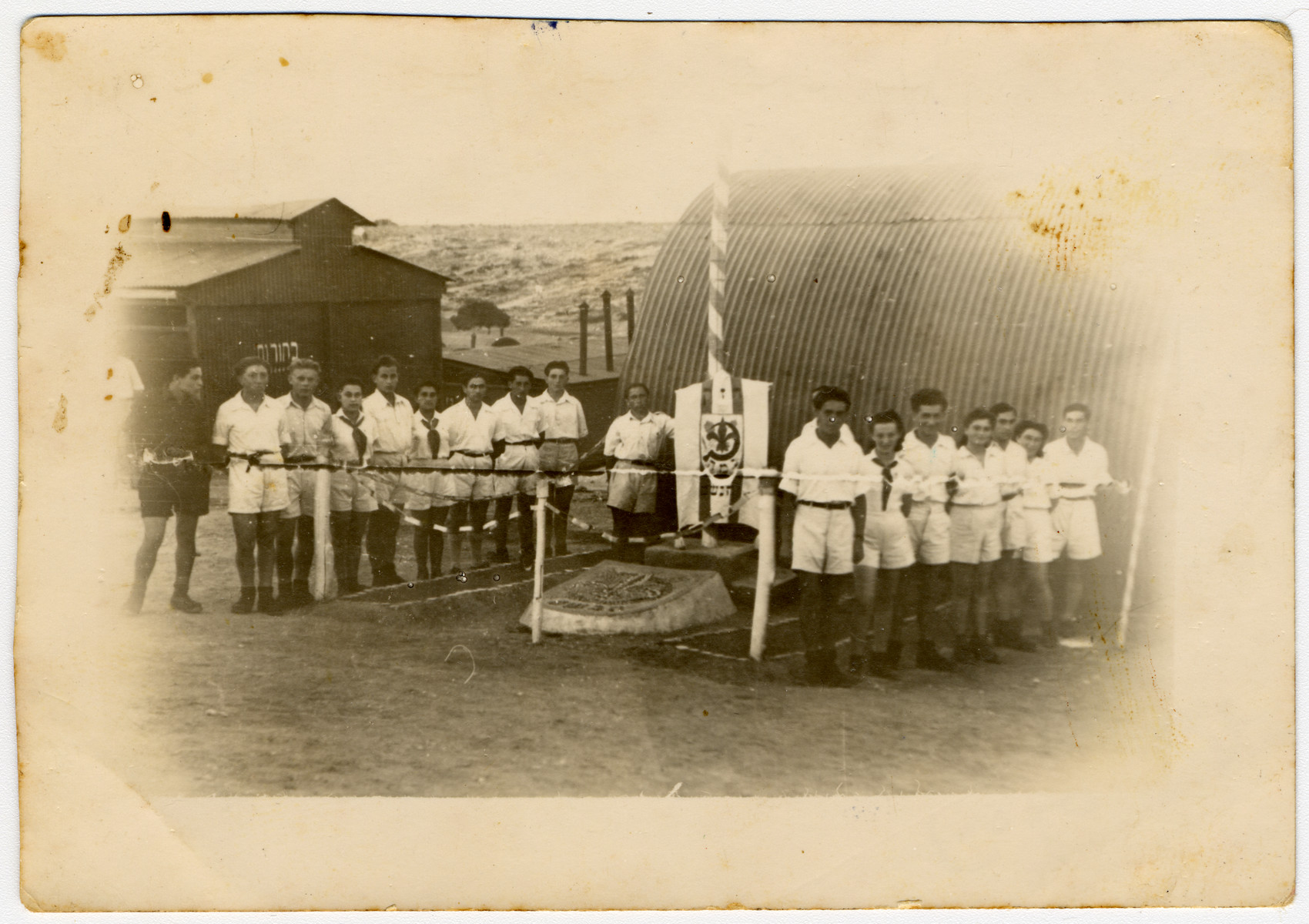 Group portrait of members of Gordonia Zionist Youth movement standing next to a flag pole in the Cyprus internment camp.