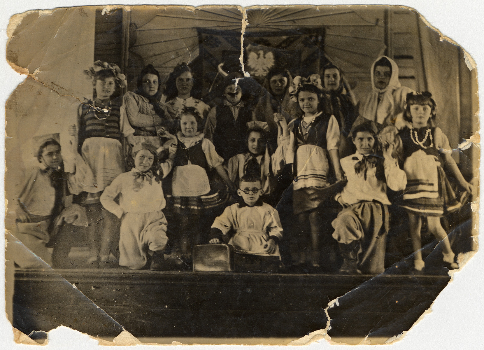 Group portrait of children, many of whom are Jewish refugees, performing on stage in traditional Polish folk costumes.   Among those pictued is Esther Szulc, the donor's wife (first from the right in the front row).