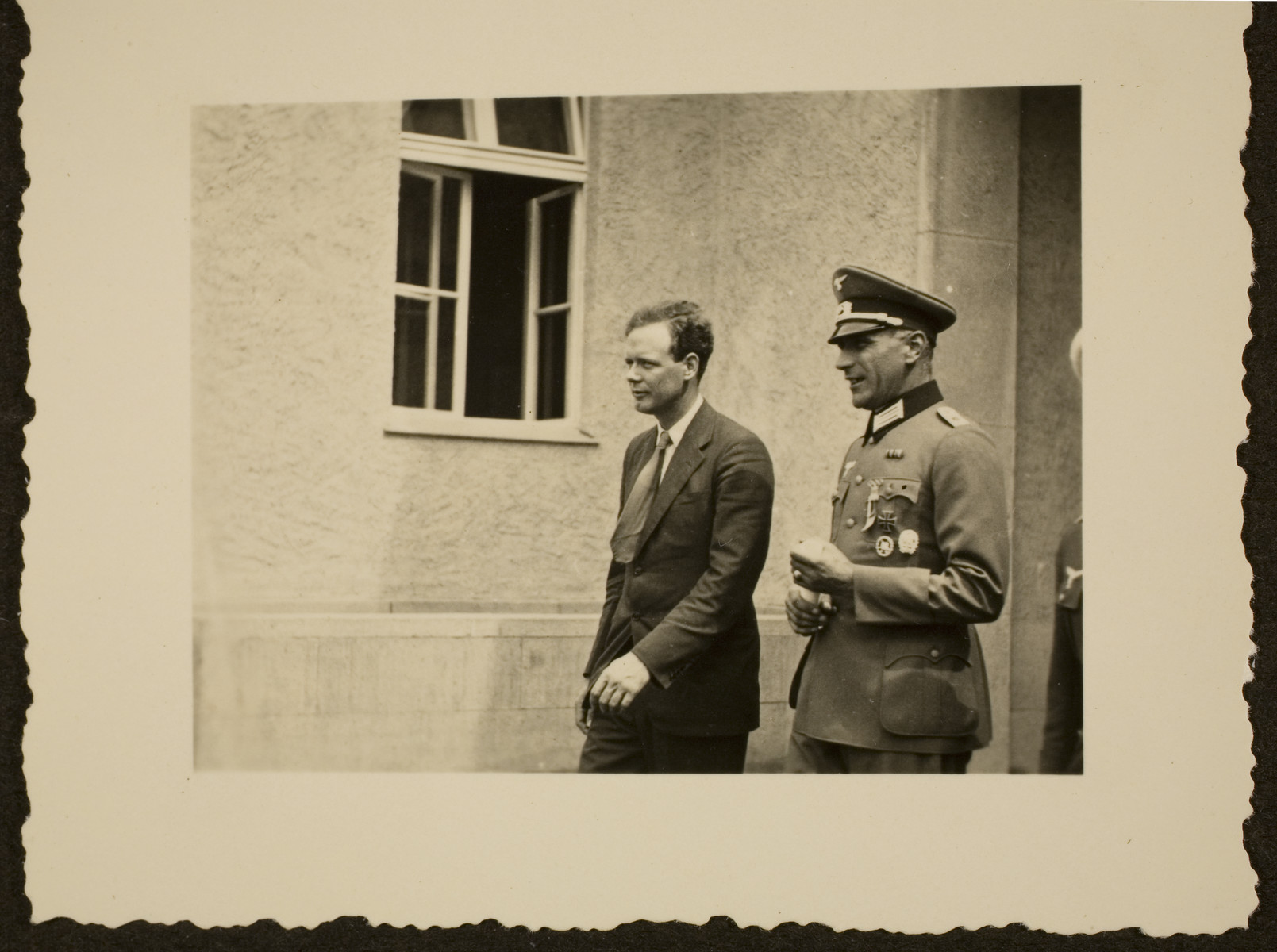 Charles Lindbergh, accompanied by a Nazi officer, walks past a building during the Berlin Olympics.