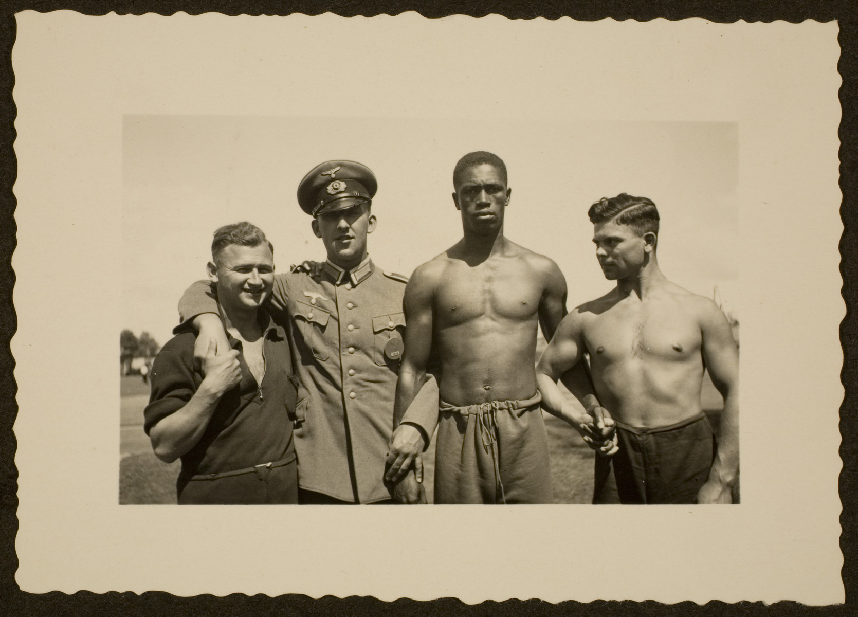 A German in an Army uniform poses with Olympic athletes.  Pictured second from the right is American track and field athlete John Woodruff.  Fritz Bezzelt (father of the donor) is pictured on the far right.