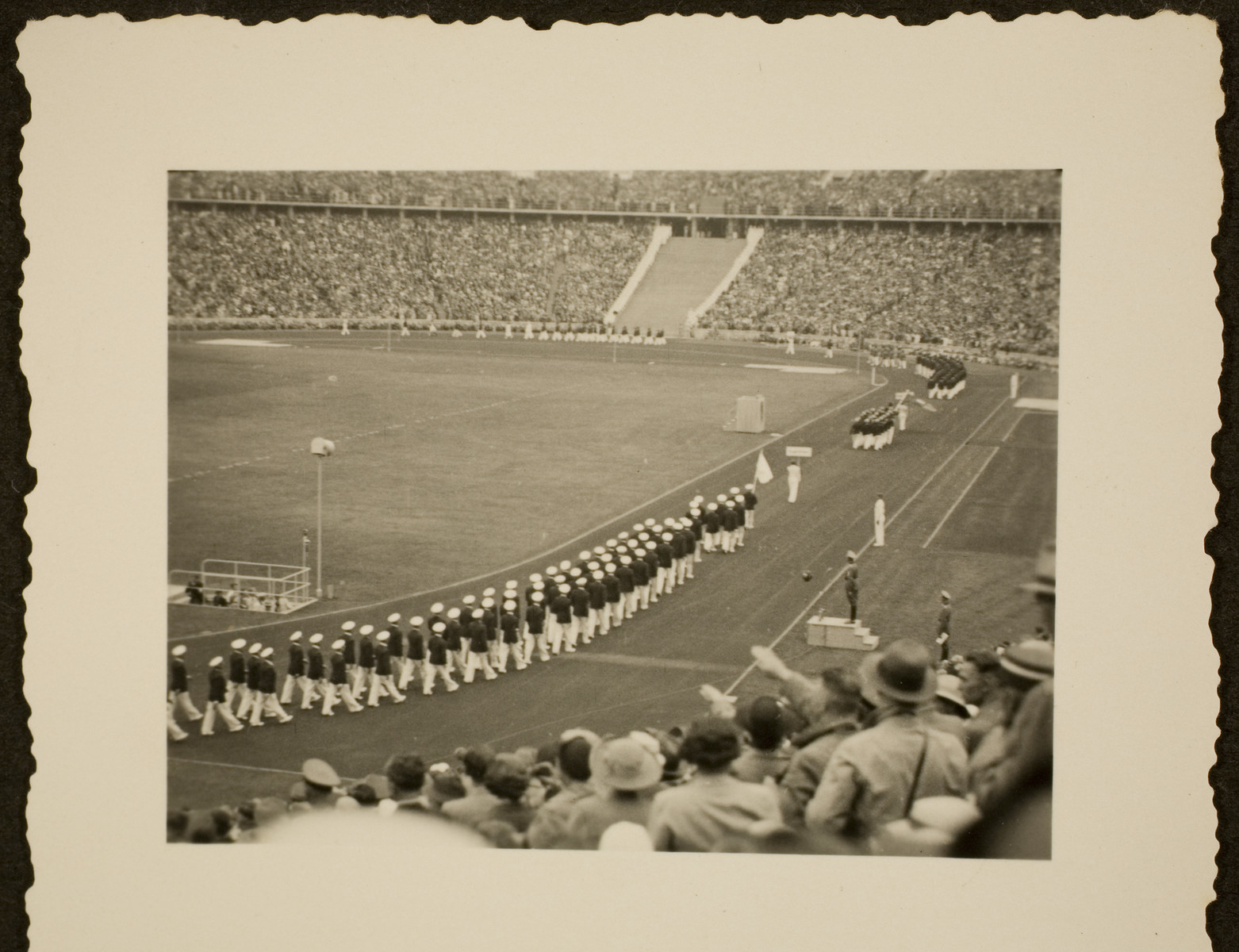 A view from the stands of the American Olympic team marching into the Olympic stadium for the 1936 games, wearing suits and hats.