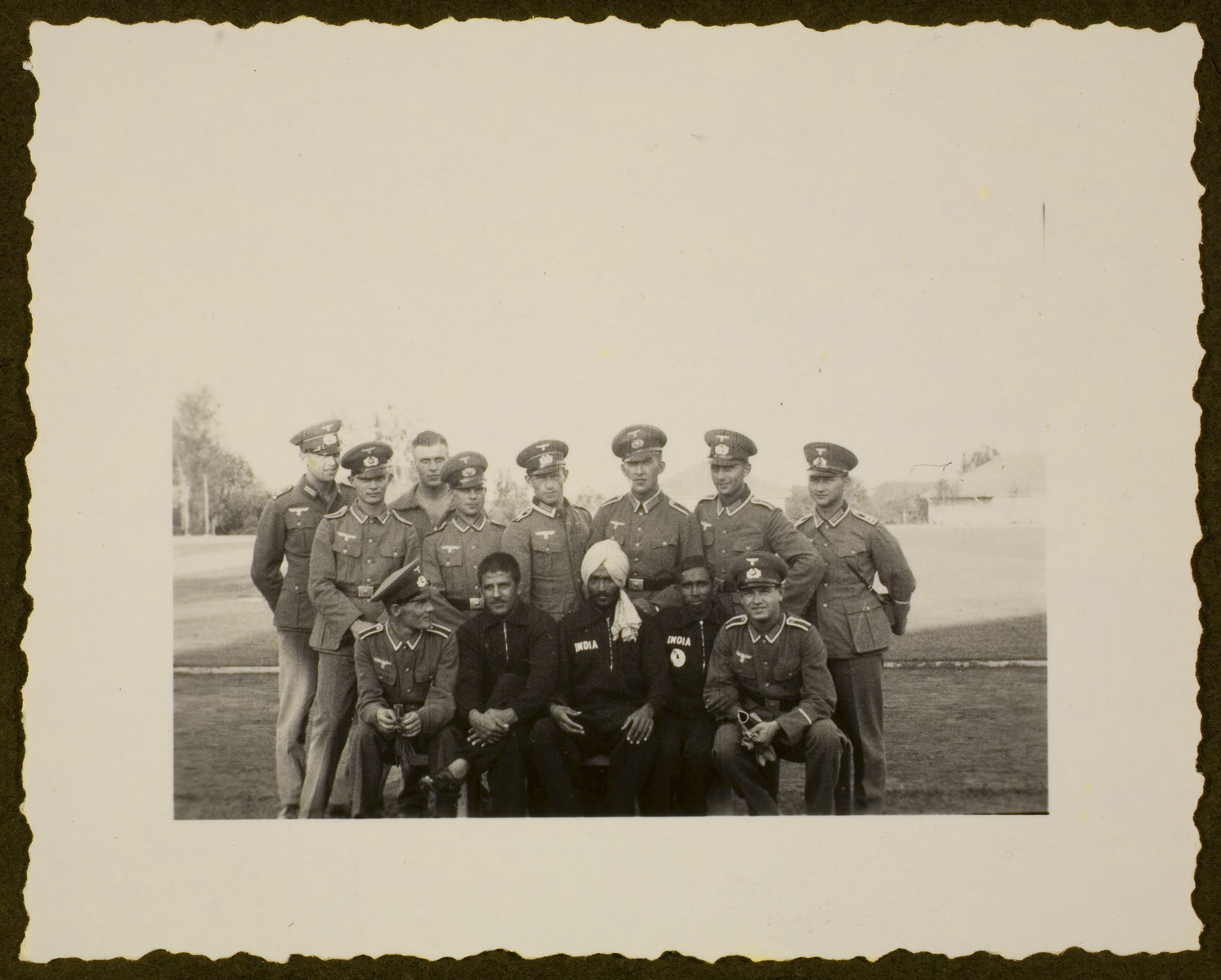 A group of uniformed German soldiers, possibly at the Olympic village, pose with three Indian Olympic athletes.