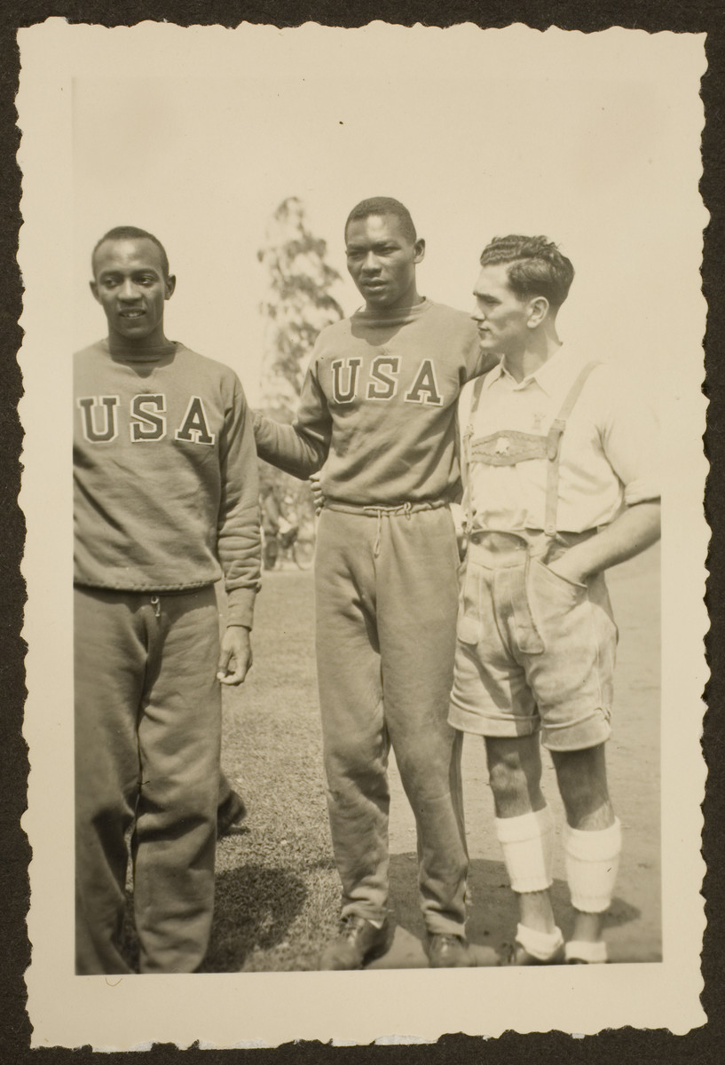Two members of the United States Olympic track and field team pose with a German citizen.  Pictured are Jesse Owens and Dave Albritton.