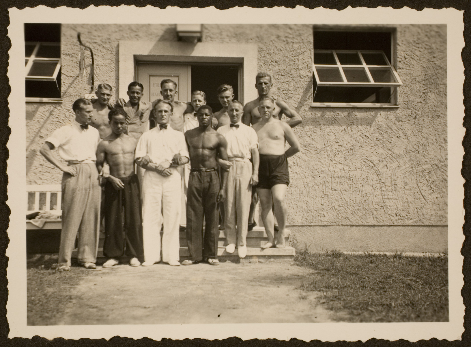 A group of athletes pose in front of one of the residences in the Olympic village.  Among those pictured is American athlete, Archie Williams, fourth  from the left.   The identities of the other athletes is unknown.
