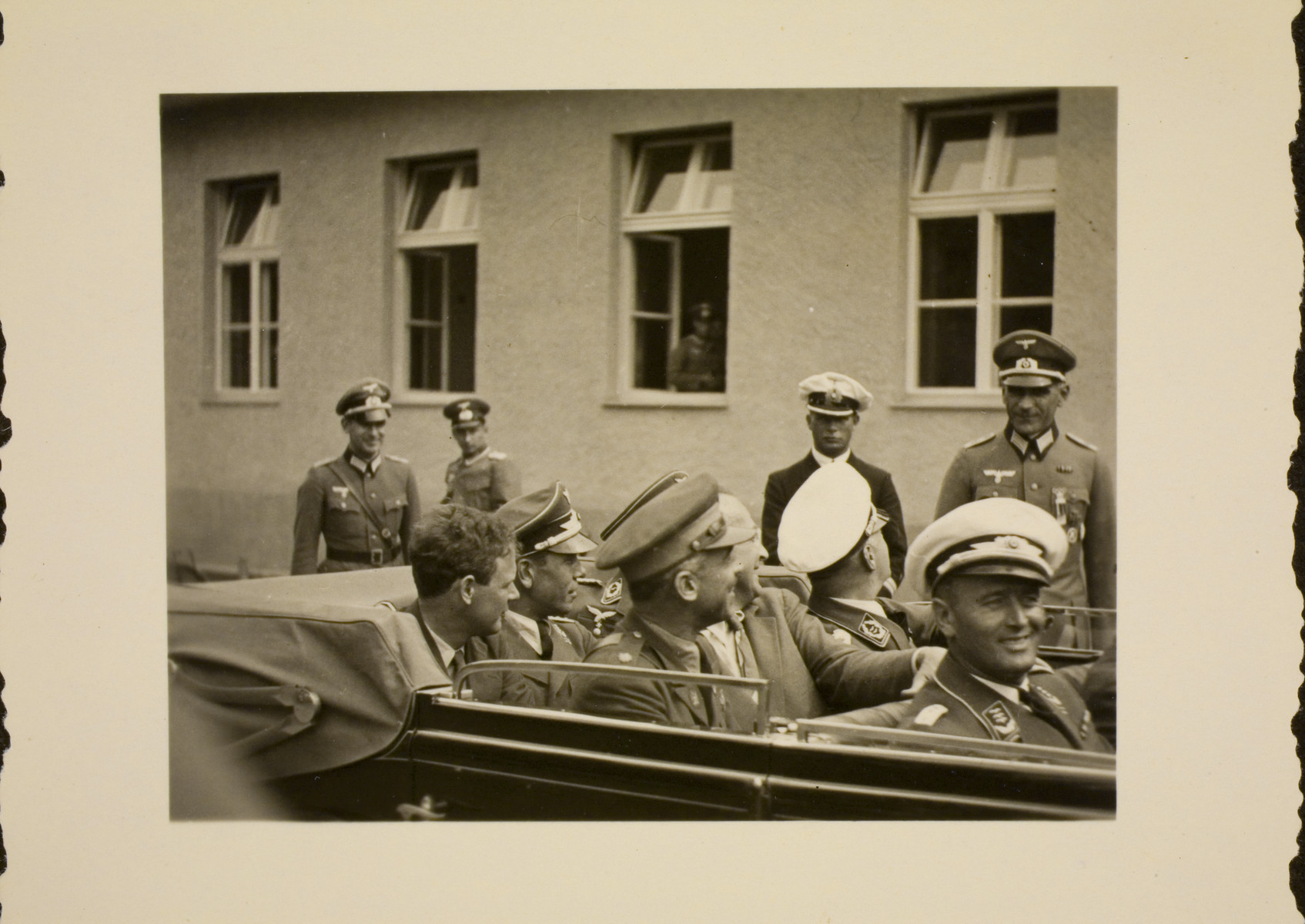 Charles Lindbergh rides in an automobile with Nazi officials upon his arrival at the Berlin Olympics.