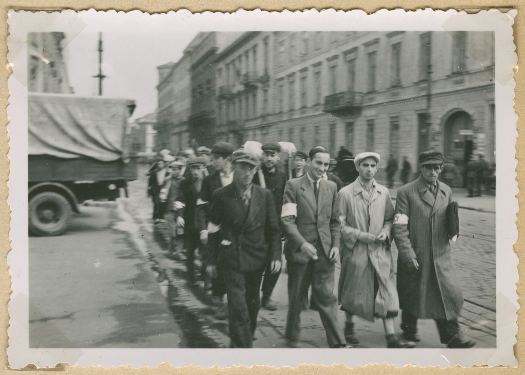 A group of Jewish men wearing armbands and some carrying shovels marches off for a labor assignment in an unidentified Polish city.