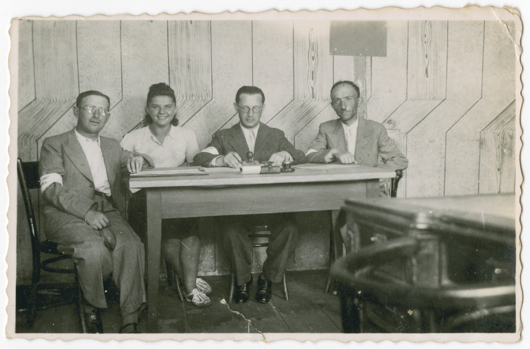"Members of the Jewish Council in Chmielnik seated at a table.   Pictured from left to right are ""Scyzoryk,"" Bluma Kleinhandler, Abram Langwald (president), and Chaim Dab (Domb, secretary)."