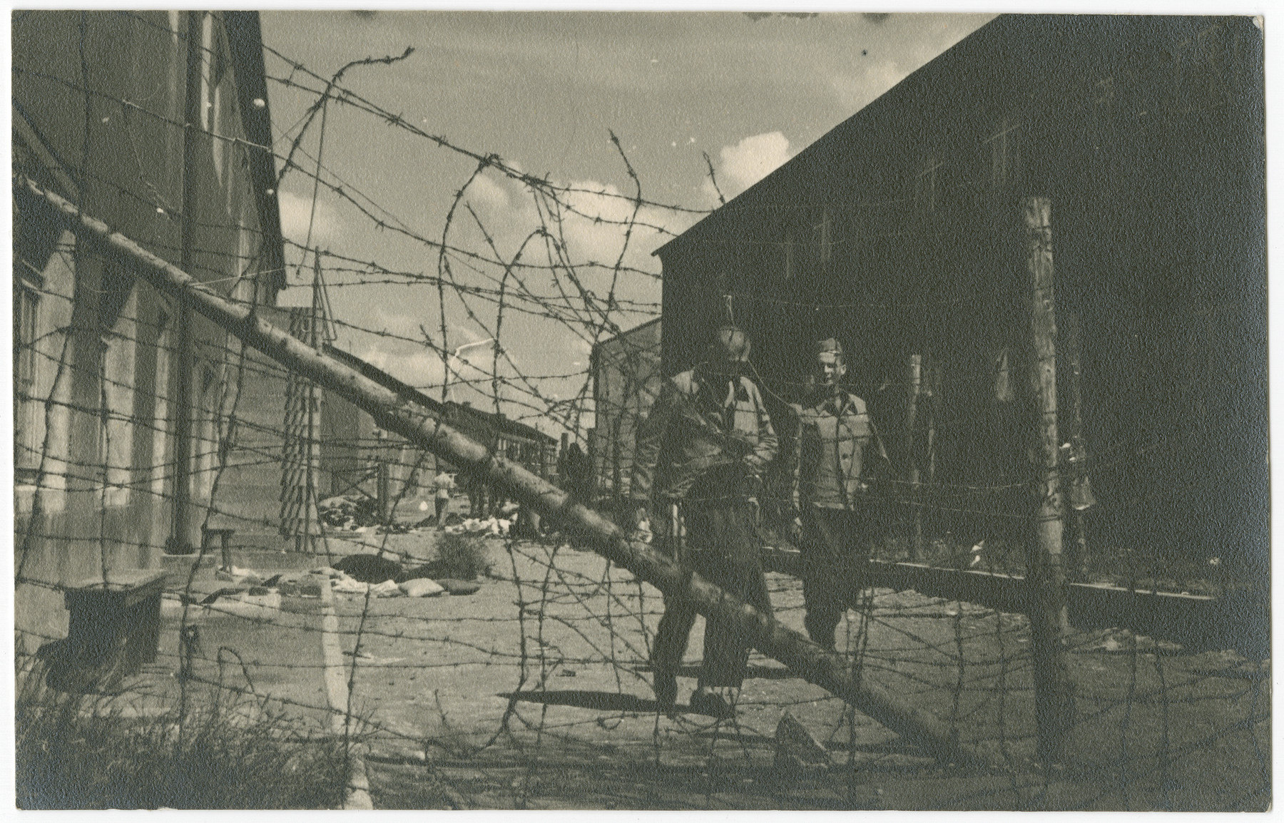 Two survivors of the Buchenwald concentration camp walk between the barracks in front of the barbed wire fence following liberation.