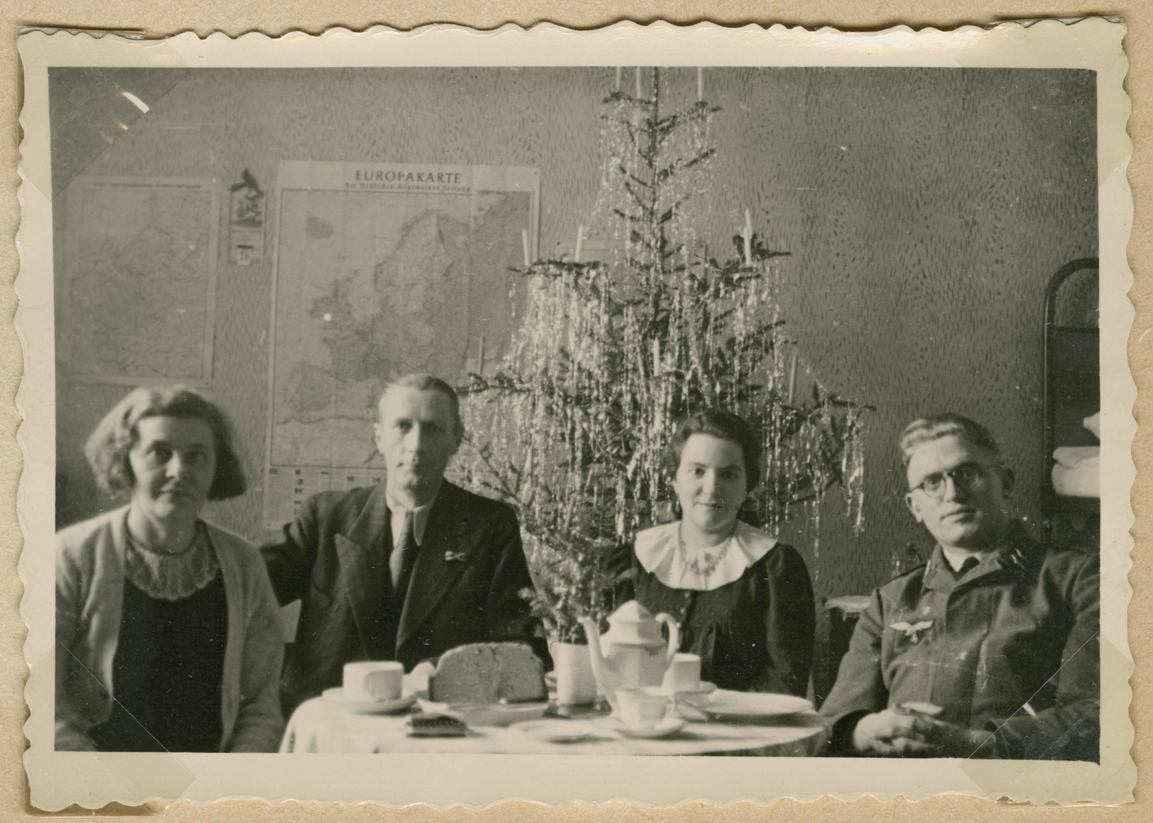"German soldiers and their families celebrate Christmas.  A map of Europe is posted on the wall behind them.  The original caption  reads ""Our room."""