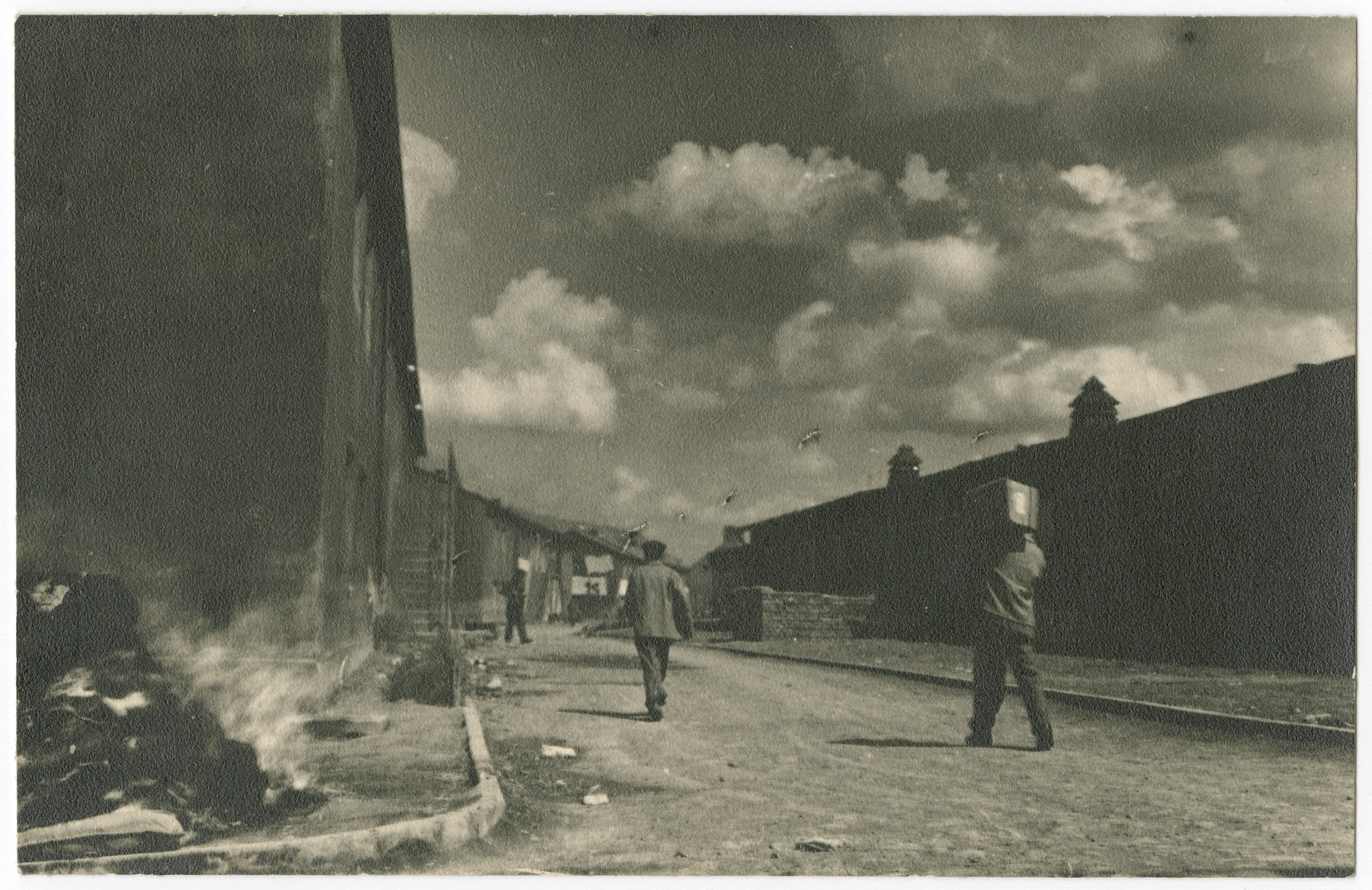 Survivors walk past the barracks of the Buchenwald concentration camp while a small fire burns on the side.