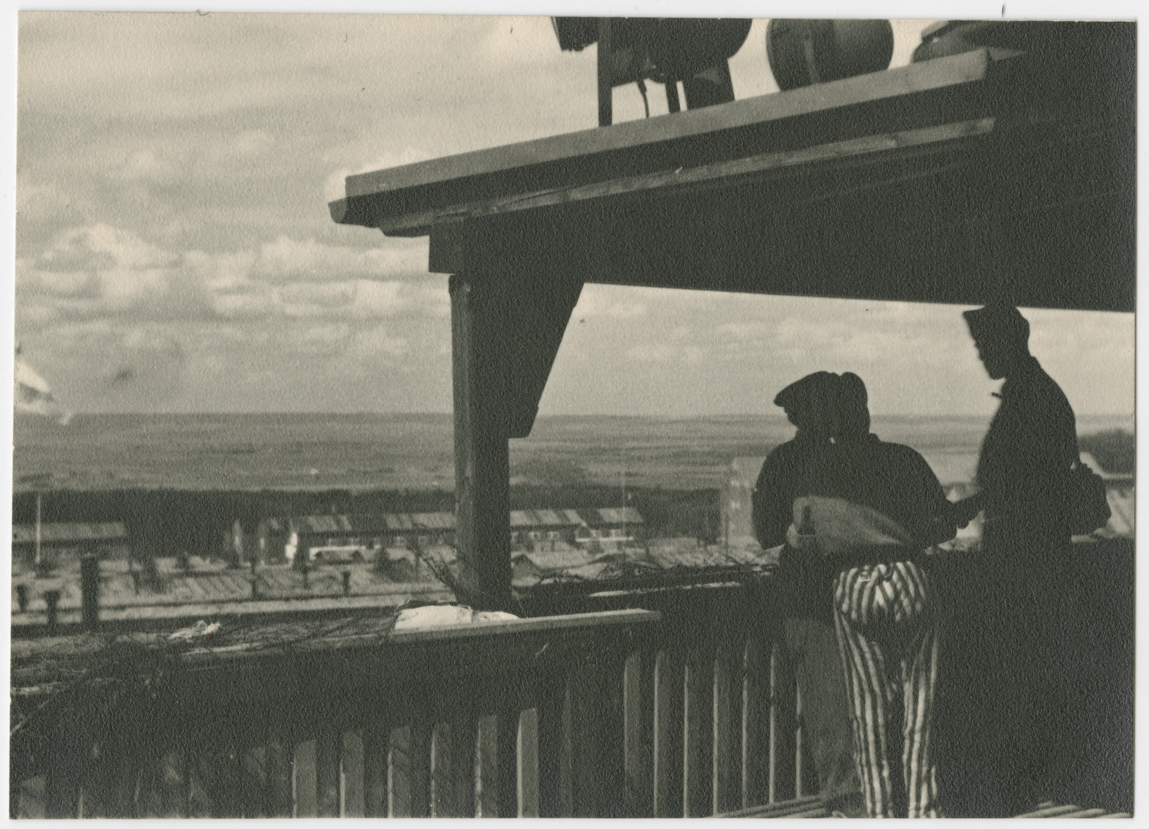 Survivors standing on an observation deck look down on the Buchenwald concentration camp.