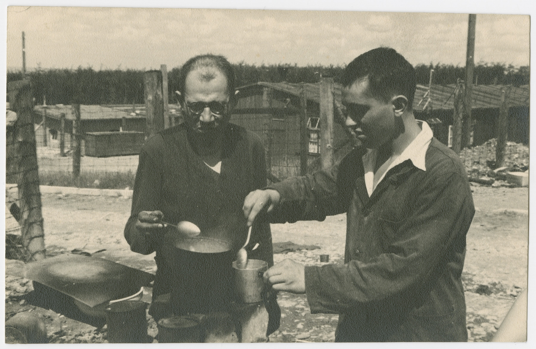Two survivors of either Ohrdruf or Buchenwald concentration camp prepare a light meal after liberation.
