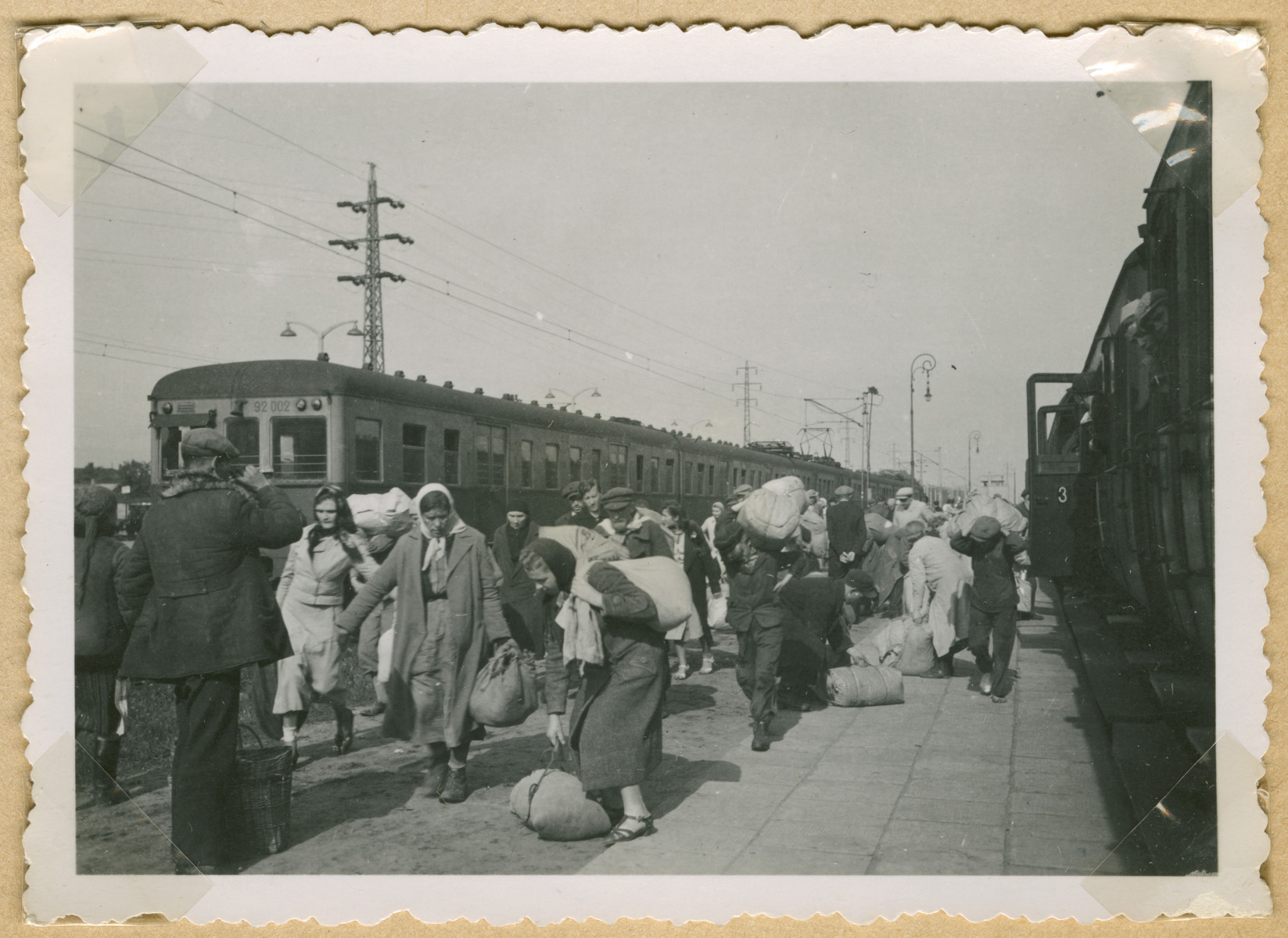 Men and women carrying bundles walk down the platform of a train station in an unidentified Polish city.