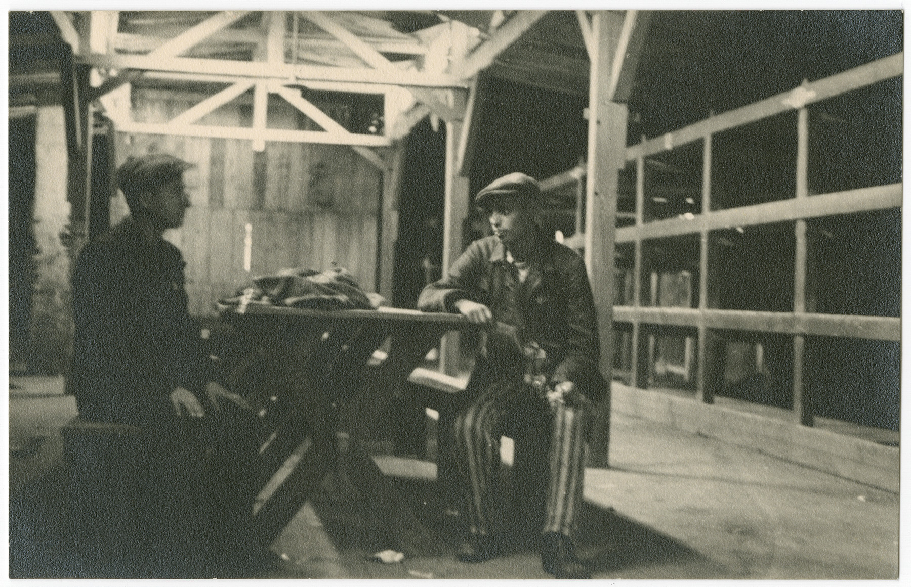 Two survivors of the Buchenwald concentration camp sit at a table inside a barrack following liberation.