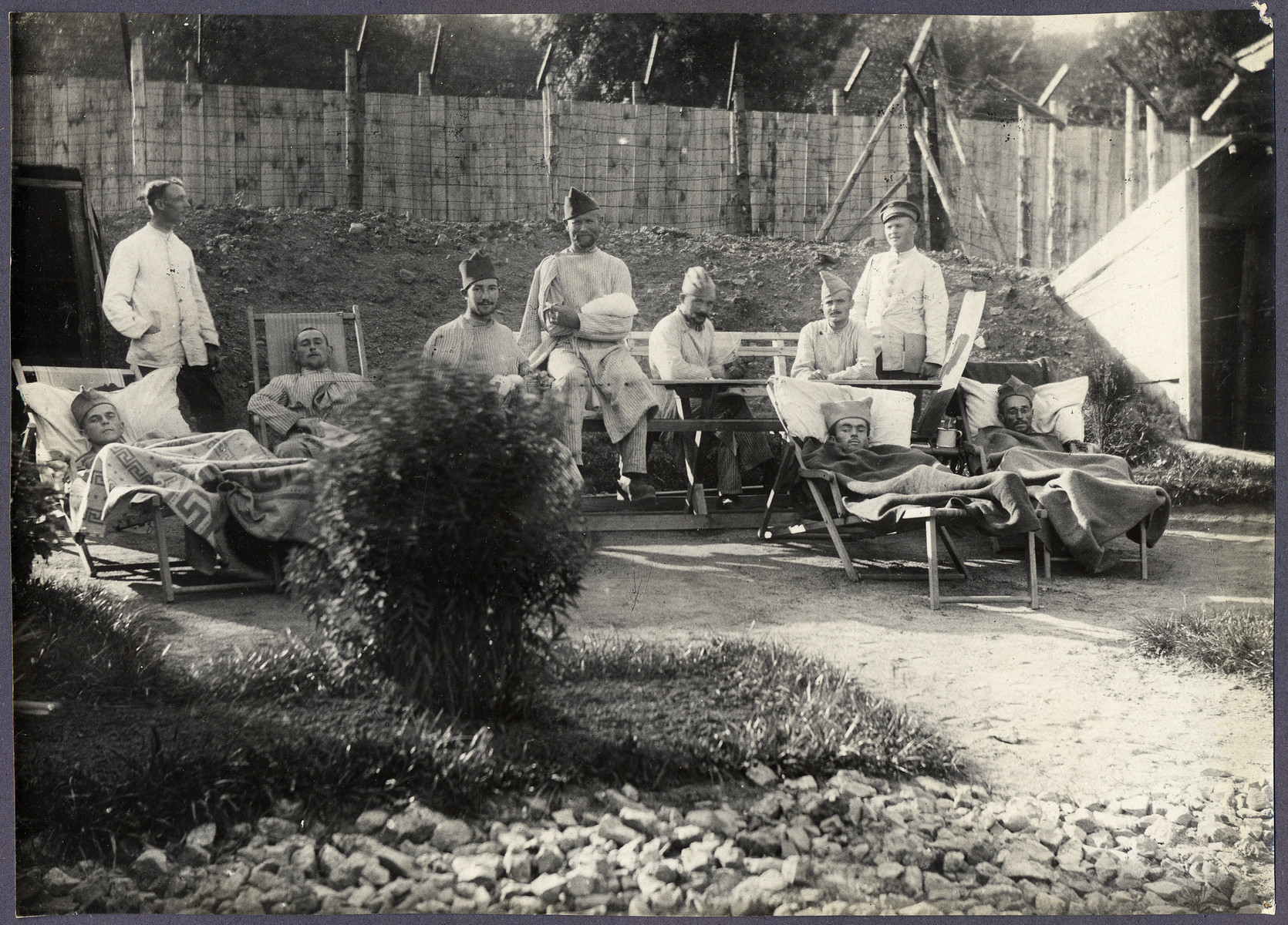 World War I POWs, many in French Army caps, relax outside in a military hospital at a prisoner of war camp.