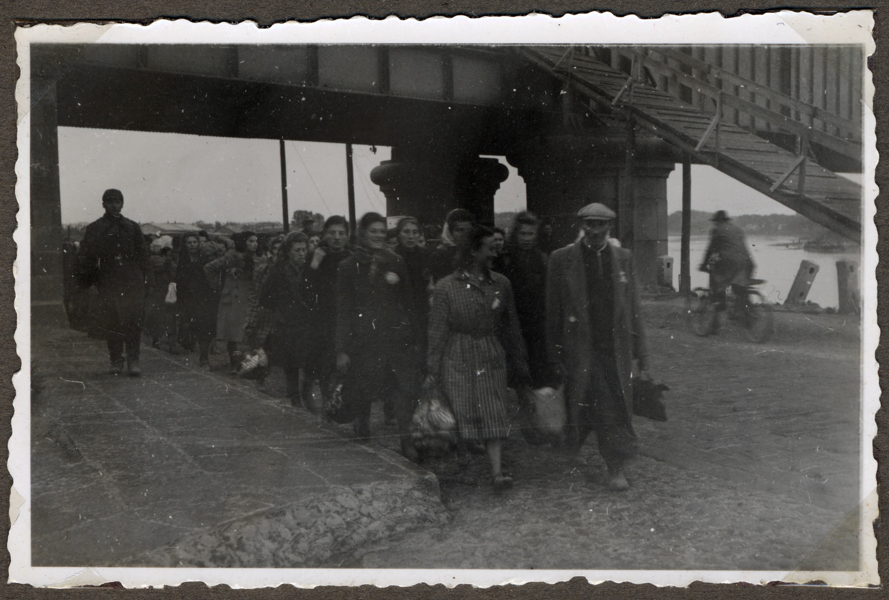 Jews wearing stars of David march under guard to the  new ghetto located across the river in Slobodka.