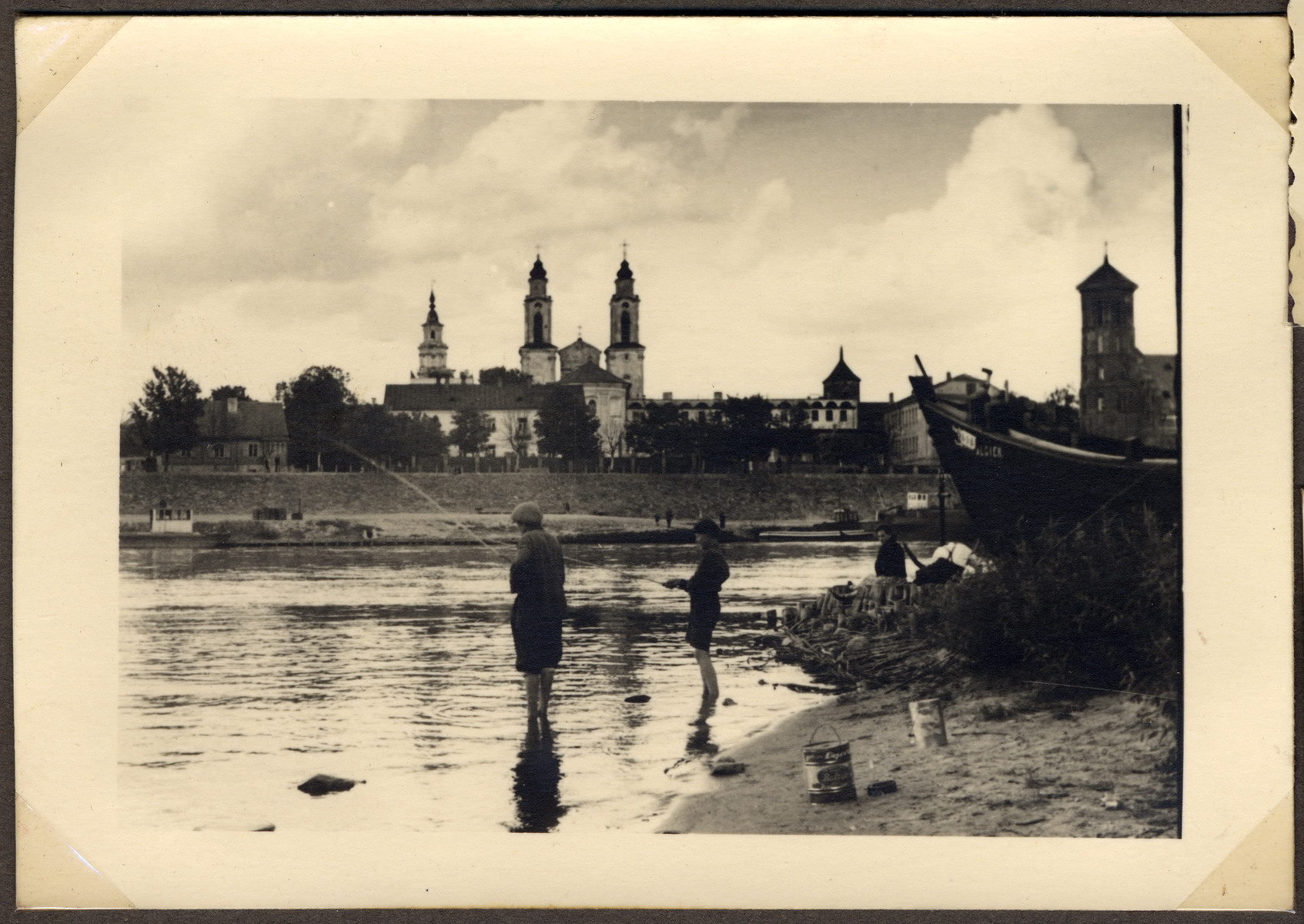 Two people stand on the banks of the river in Kaunas fishing.