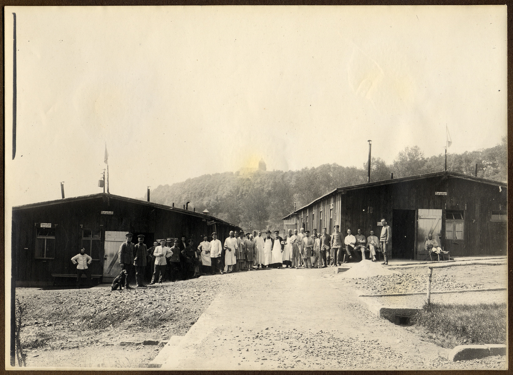 Prisoners and German camp personnel pose before barracks at a POW camp in Montmédy, France during World War I.