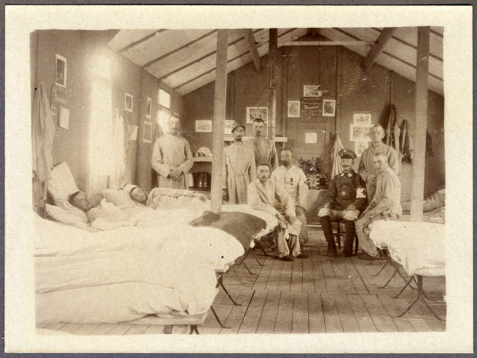 Patients [possibly POWs, ] and mGerman medical officers inside a wooden hospital room.