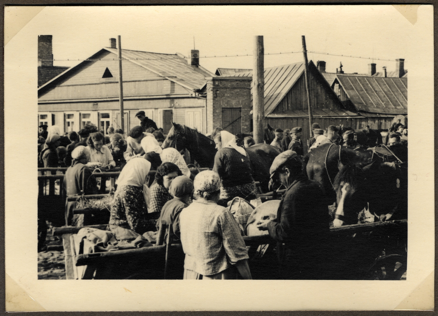 Lithuanians and Jews barter and sell goods [probably in a public square in Slobodka] during the move of Kovno's Jews to the ghetto.