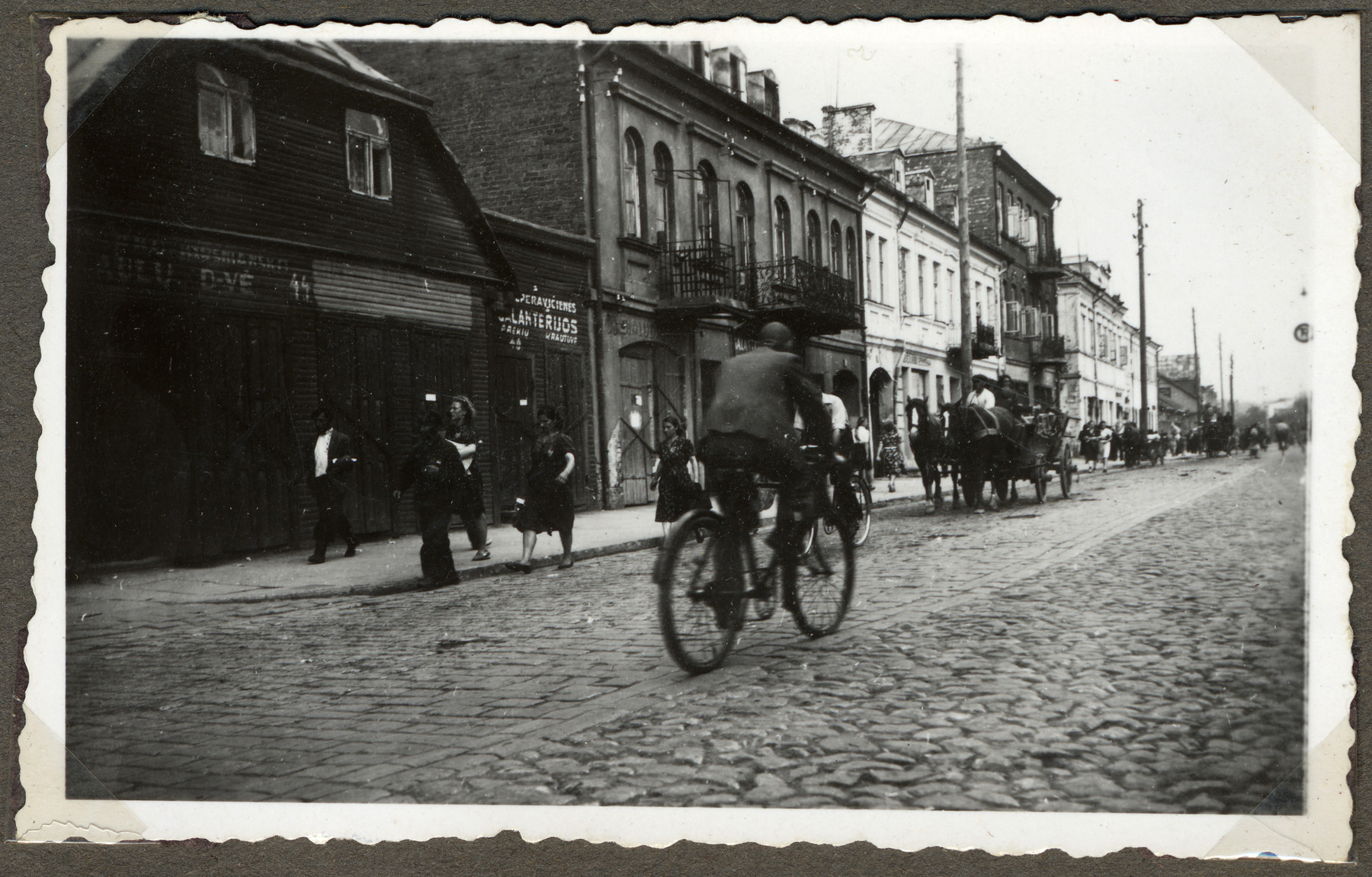 A Lithuanian man rides his bicycle down a street in Kaunas while in the other direction Jews move their belongings on carts and wagons to the new ghetto located across the river in Slobodka.