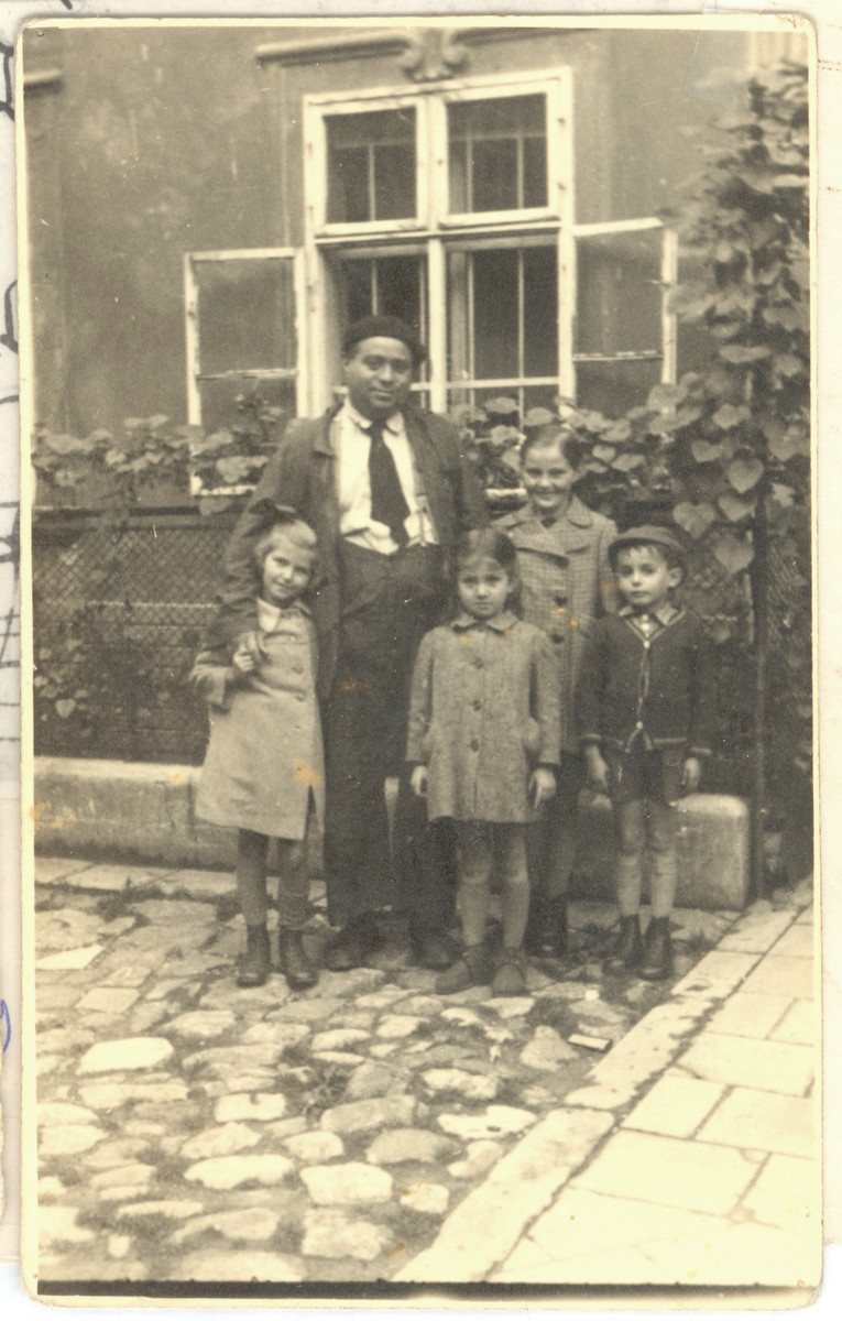 Jonas Eckstein poses with Jewish orphans from Poland that he sheltered after they were smuggled over the border into Slovakia.  Among those pictured are Miriam Ater Ovide (front left) and her sister Lola Ovide (back, center.).