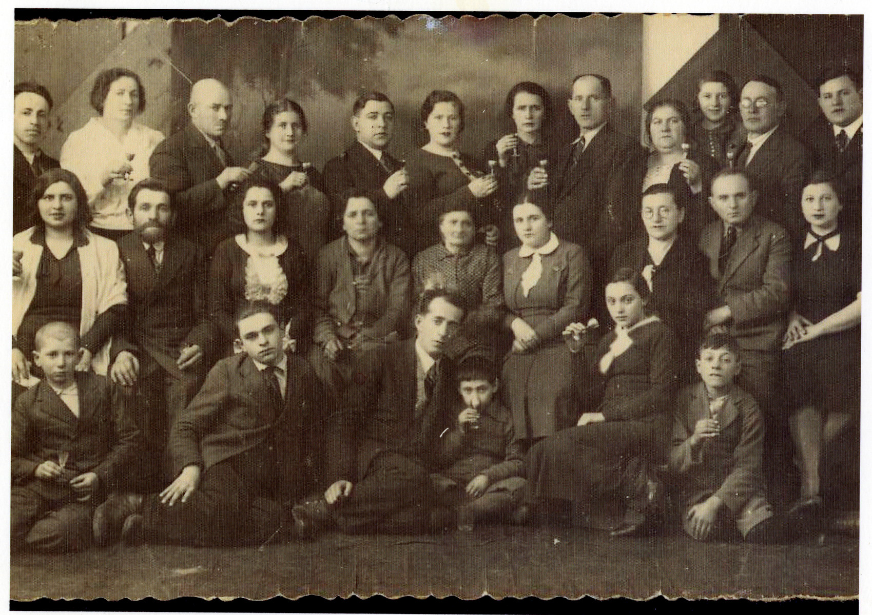 The extended maternal family of Sara Borzykowski celebrate the impending emigration of a cousin.    Pictured are members of the Krause family and Wilhelm families (Sara Fogelman's maternal relatives).  Among those pictured are Hersh Fogelman (5th from left, top row) and his wife Sara Fogelman standing next to him.  Wolf Borzykowski (Sara's brother) is standing on the top row, far right.