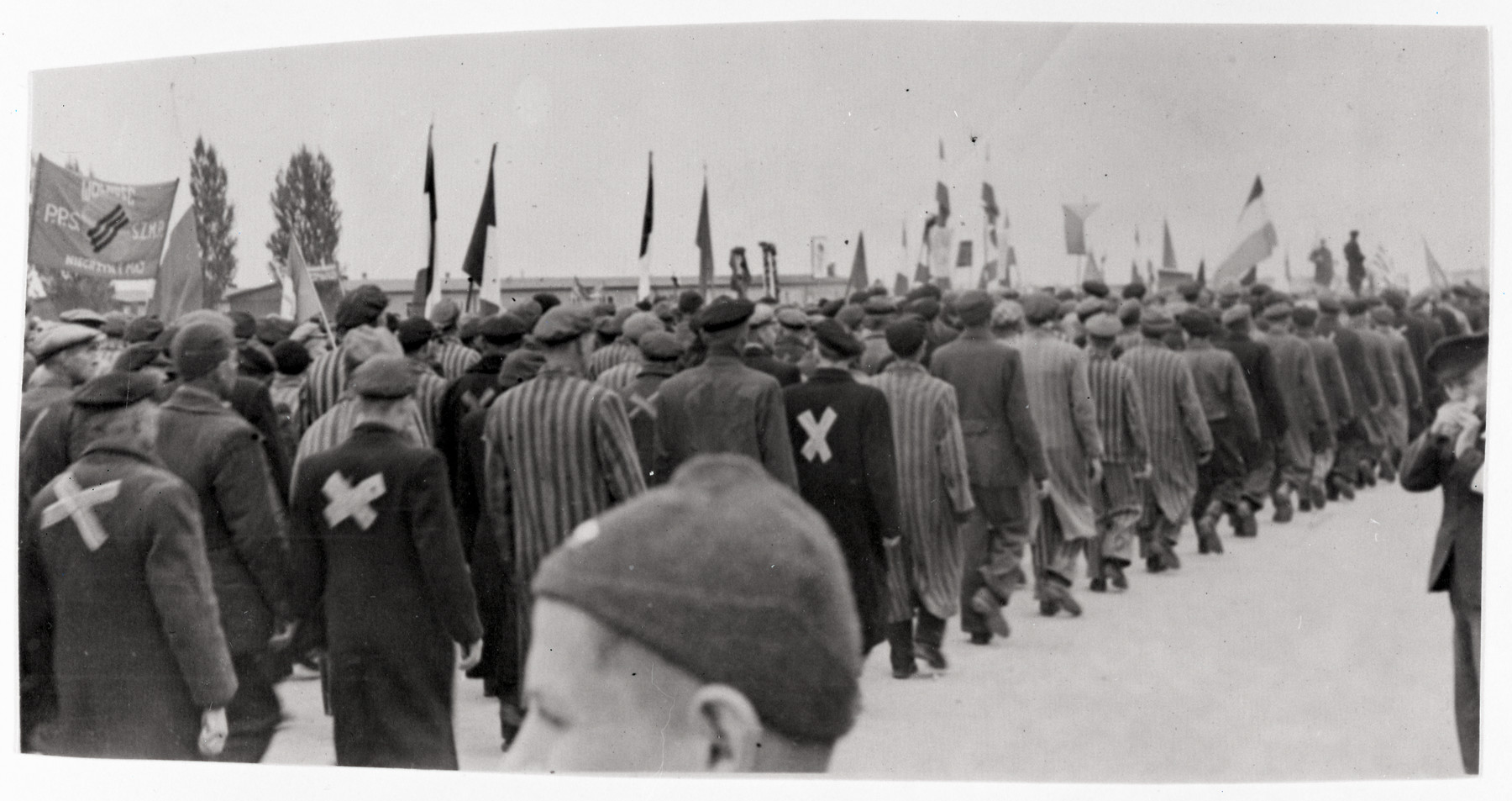 Prisoners of various nationalities march to a memorial service at the Dachau concentration camp shortly after liberation.