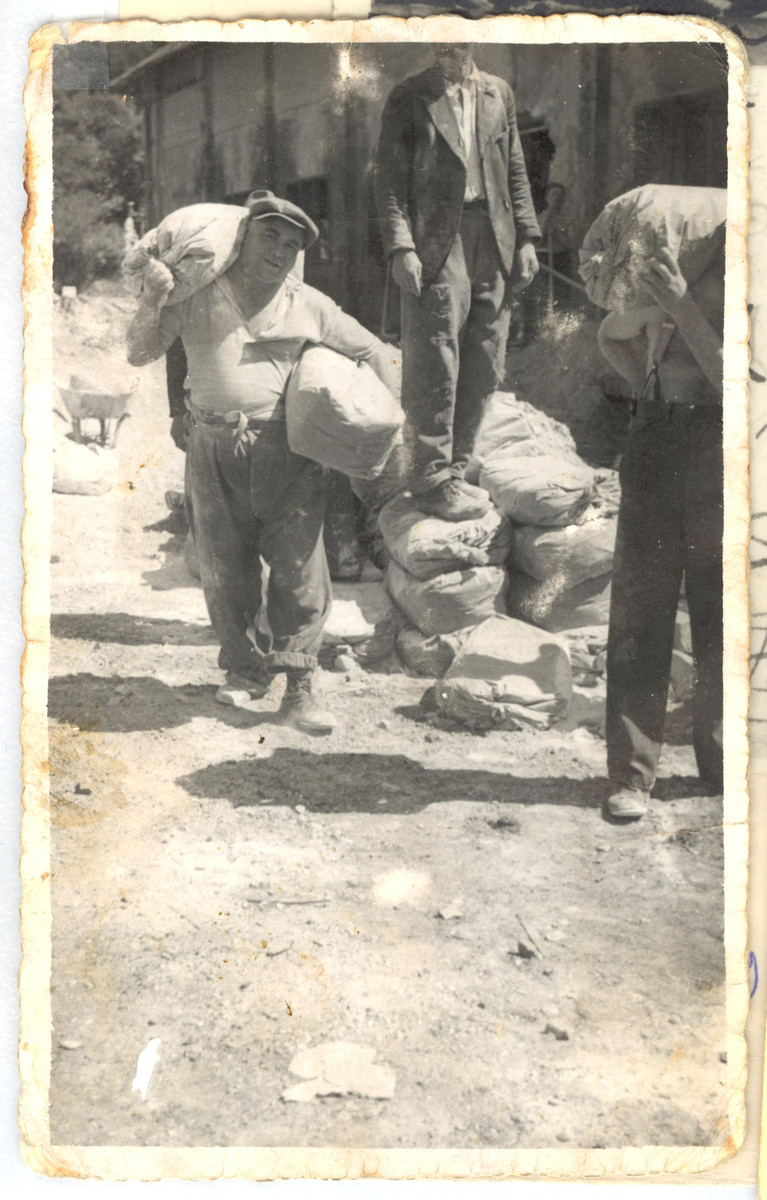 Jonas Eckstein hauls two bags of cement in a labor camp in Slovakia.