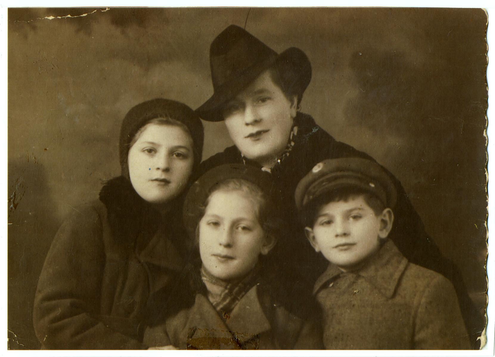 Studio portrait of Sara Fogelman and her three children in prewar Radomsko, Poland, shortly before the war.  Pictured are Pola (left), Genia (bottom), Abraham Joseph (far right), and their mother Sara (top.)