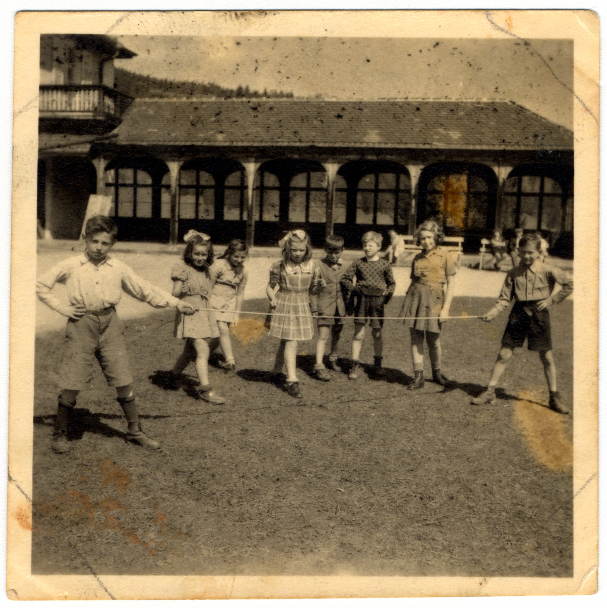 School children play a rope game in the Feldafing displaced persons' camp.  Among those pictured holding the rope are the Shmulevitch brothers, then left to right are Sally Bass, Rifka Lifschitz, Ada Rosenberg, others unidentified.