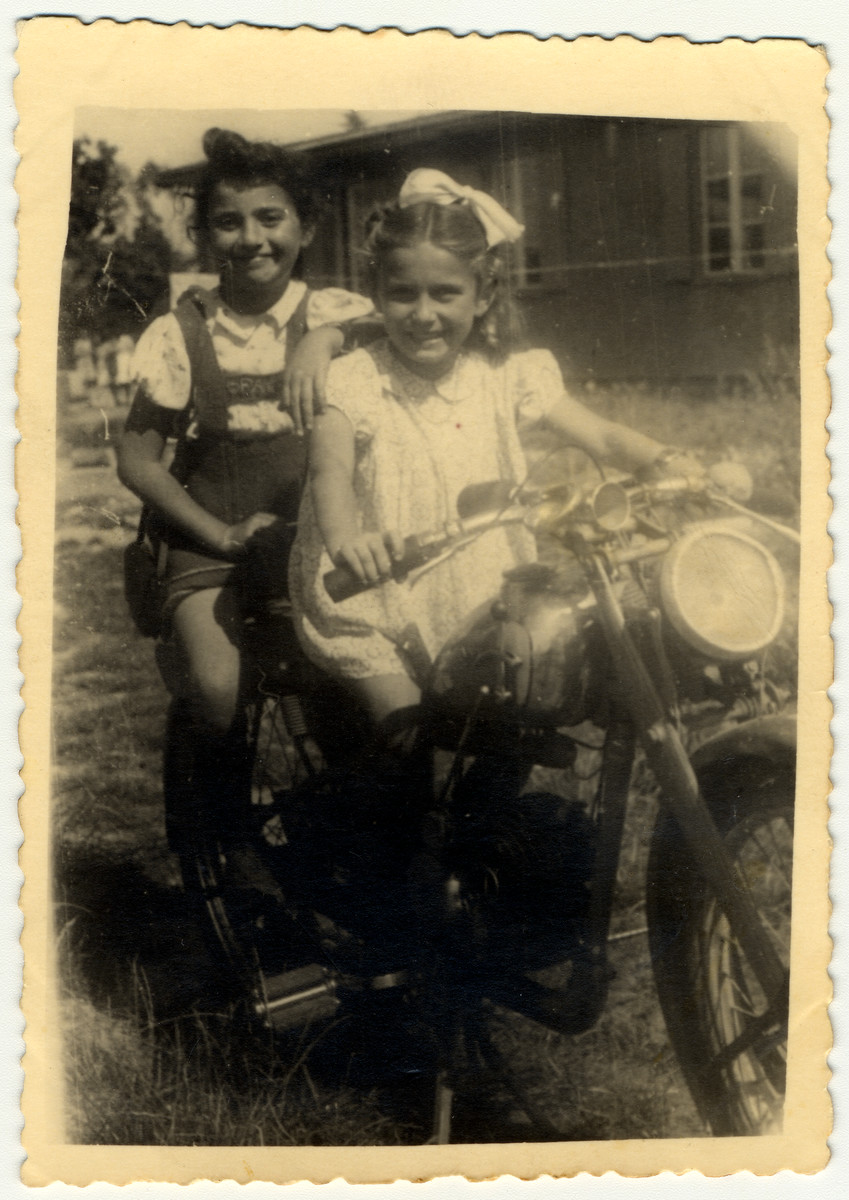 Two young girls pose on a motorcycle in the Landsberg displaced person's camp.  Pictured are Feigele Meichlowitz (cousin of the donor) and her friend Leah.  Feigele was the daughter of Esther Meichlowitz (the sister of Avraham David).