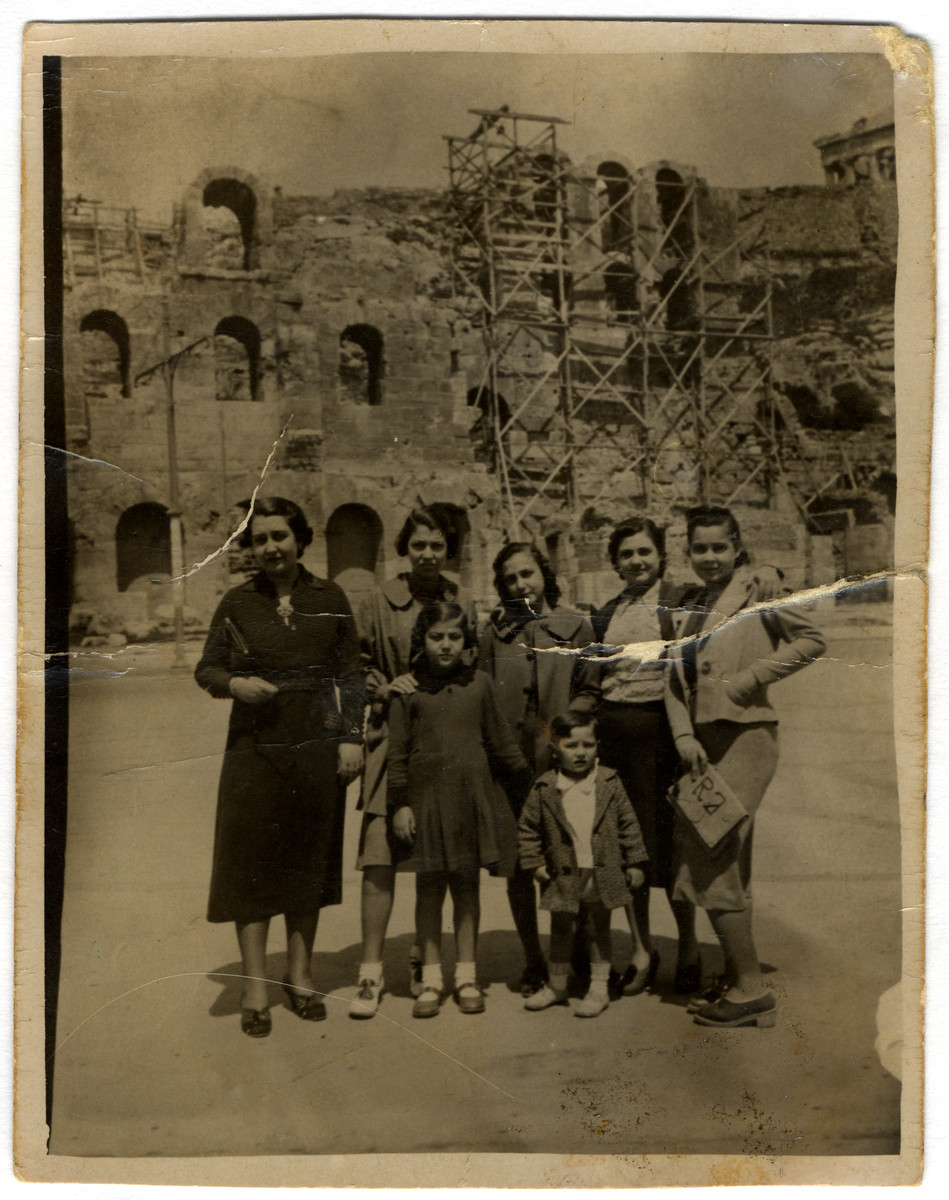 A  Greek Jewish family poses in front of a building in ruins.   Among those pictured are Claire Jesurun (later Elhai), and her siblings Gilda, Renee, Susee, and Ralph.