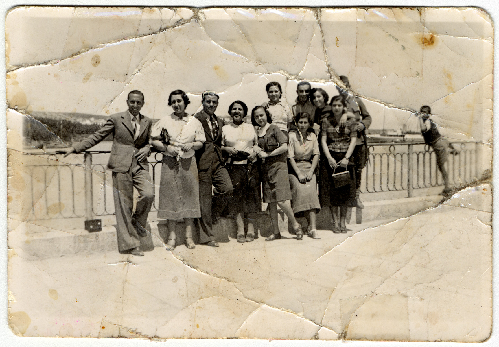 A Greek Jewish family poses next to a railing overlooking the Euboean Gulf.  Among those pictured is Claire Jesurun.