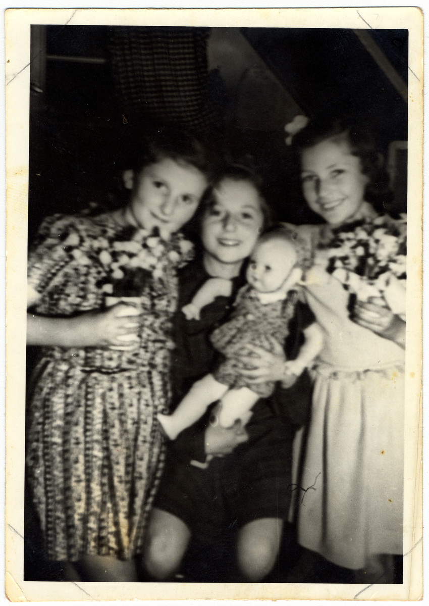 Close-up portrait of three girls in the Feldafing displaced persons' camp holding flowers and a doll to celebrate their teacher's wedding.  Pictured are Rivka Lifschitz, Leah and Rutka Kron.