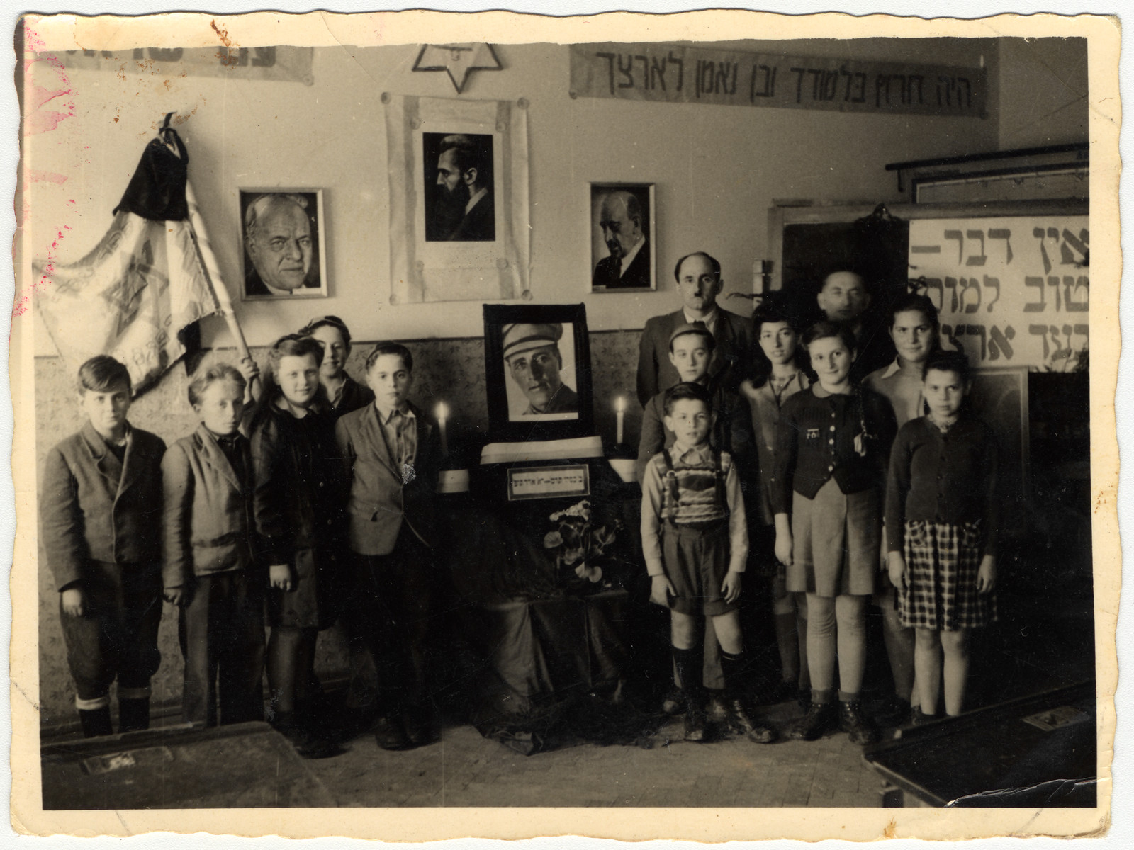 Zionist youth pose together in the Feldafing displaced persons' camp in a room decorated with Hebrew banners, a Zionist flag and portraits of Bialik, Herzl, Trumpeldor and Weitzman.  Rifka Lifschitz is standing third from the right.  Ada Rosenberg is on the left next to the flag.