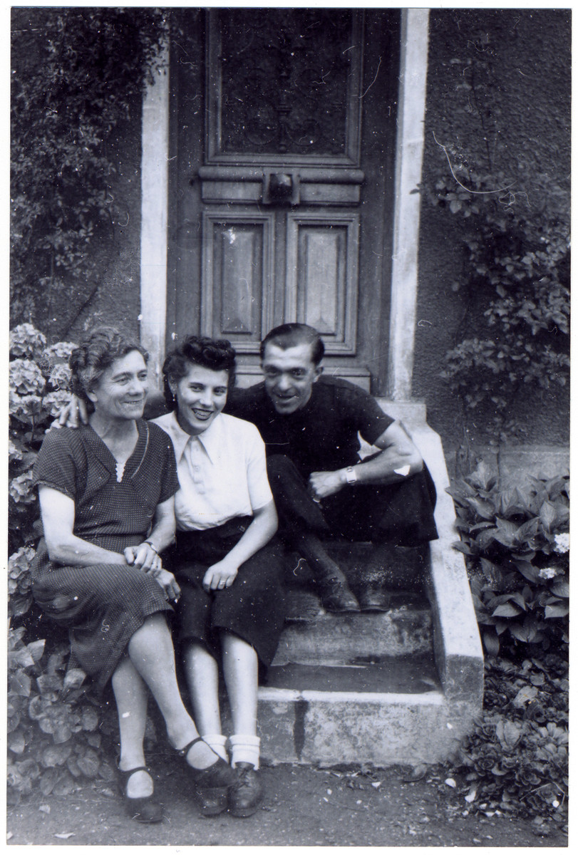 Rescuers, Albertine,Simone and Henri Voisin, rest on the steps of their home.