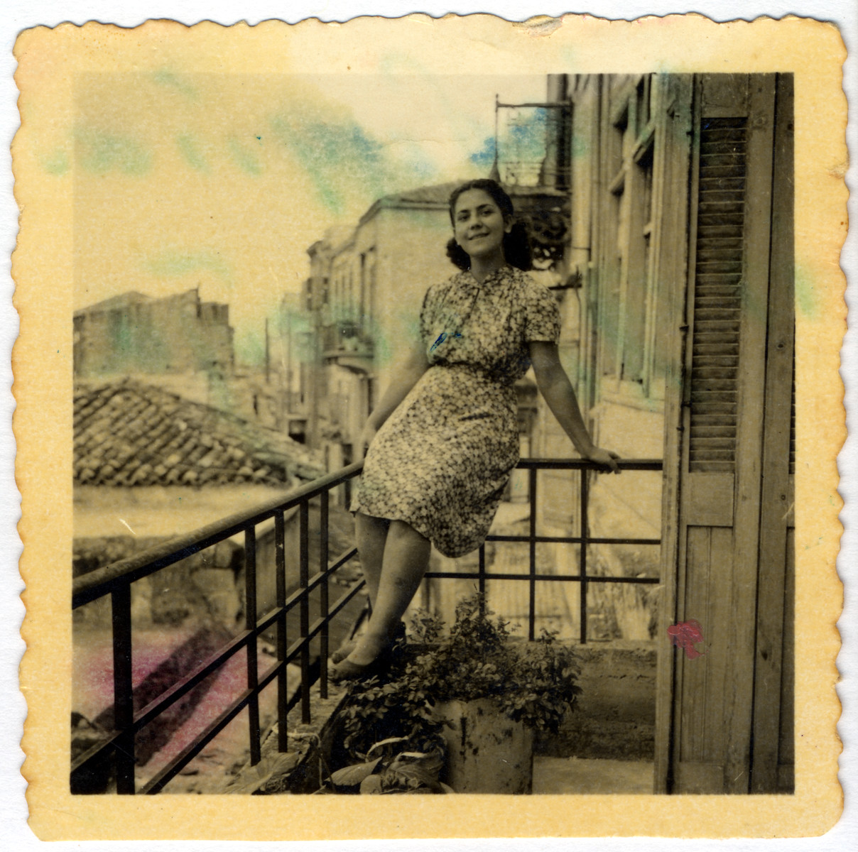 A young woman sits on a balcony railing.  Pictured is Chrissoula Elhai (?), sister of Jacob Elhai.