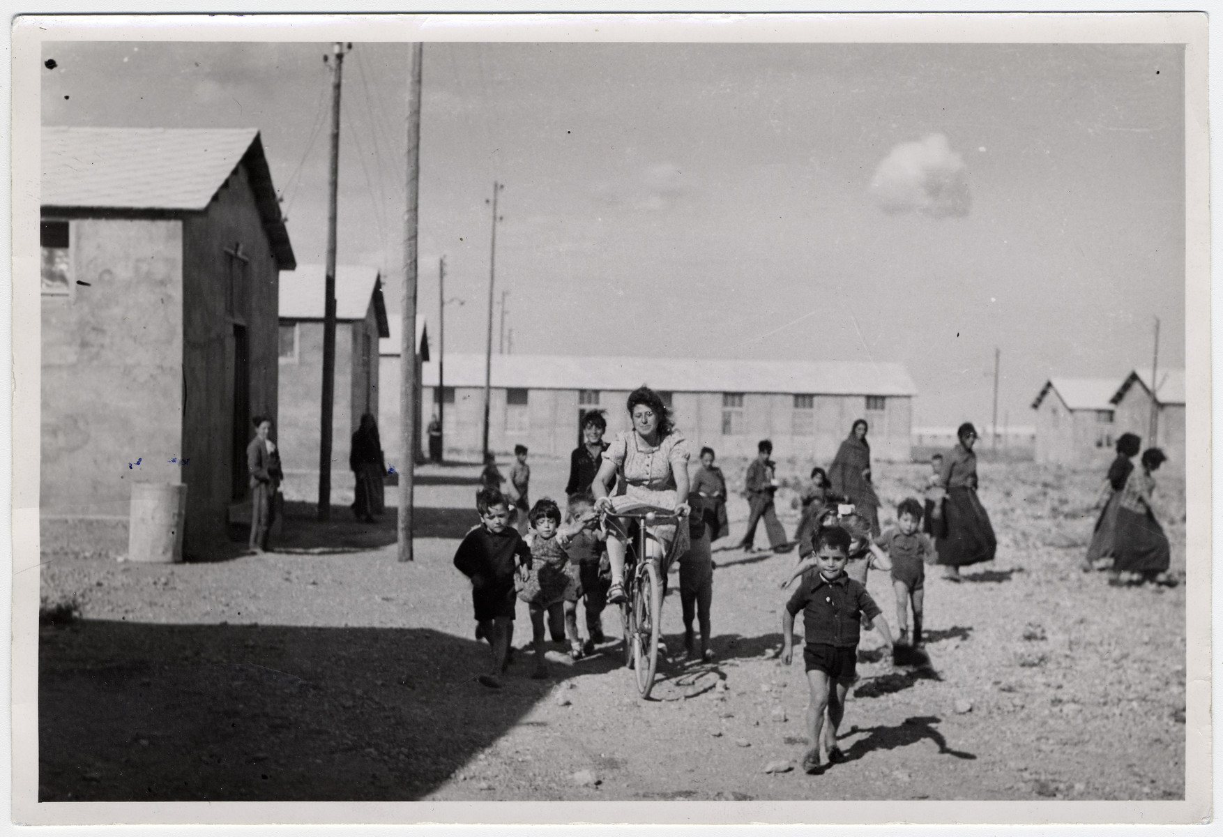 "Spanish and Roma children run alongside Jacqueline Levy who is riding a bicycle, passing various buildings at the Rivesaltes camp.   Original caption reads: ""End of class. Spaniards and Gypsies."""