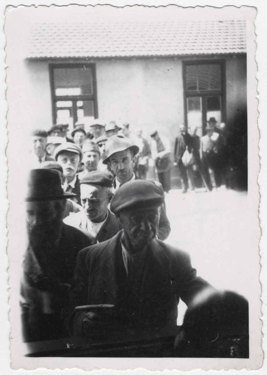 """A group of Jewish men line up to receive rations at the Rivesaltes internment camp in France.   Original caption reads: """"The line of interned Jews, before soup."""""""