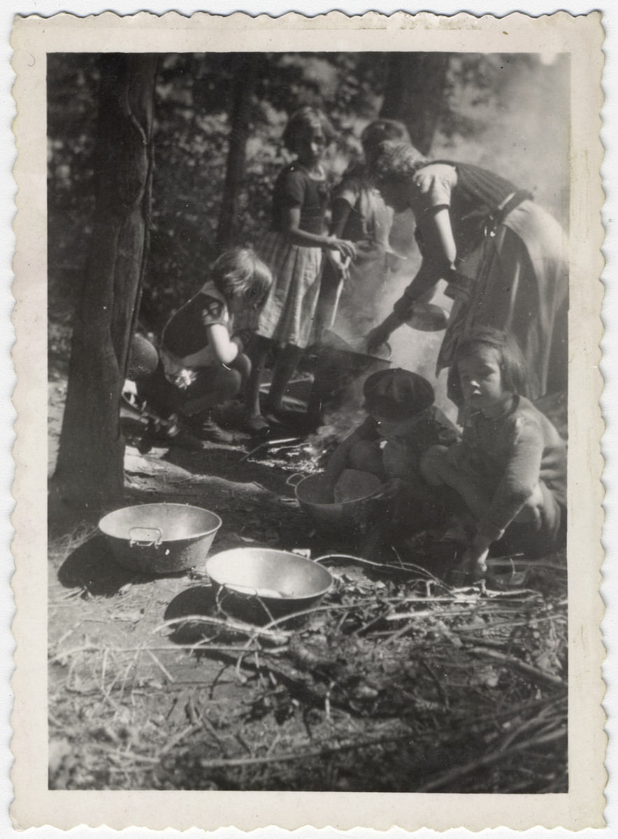 "Young girls and women cook coutdoors in a Jewish scout camp near Limoges.  The original caption reads: ""Limoges. Camp P.A.""  P.A. stands for ""Petites Aides"", those scouts who were ten and under."
