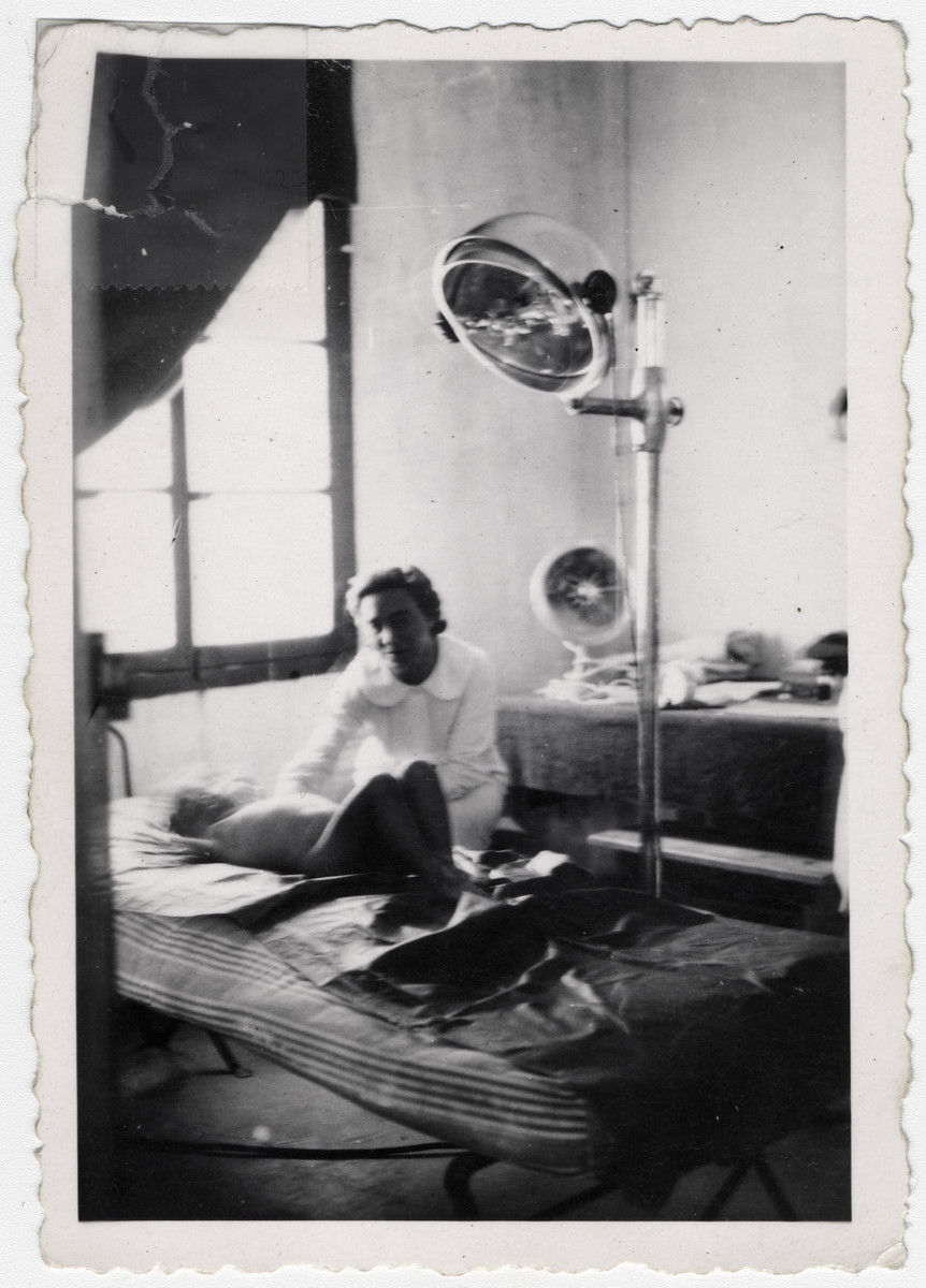 """A young child is tended by a woman while he lays down on a bed, in what is probably the infirmary at Rivesaltes.   Original caption reads: """"The single lamp in camp."""""""