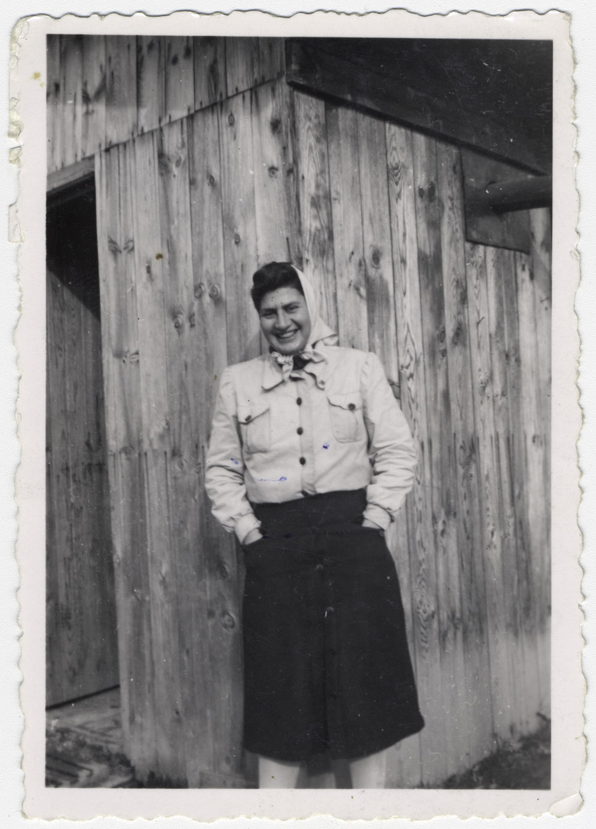 "Ruth Lambert poses in front of a wooden building at the Gurs internment camp in France.   Original caption reads: ""Ruth Lambert, Gurs Camp, December 1942."""