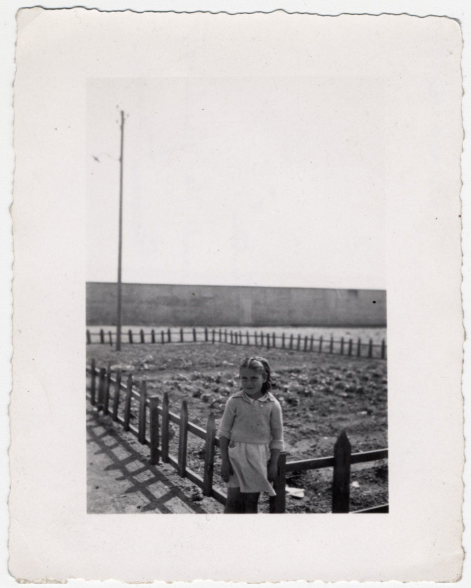 "A young girl poses in front of a small fenced in garden, provided by the relief workers at Rivesaltes.   Original caption reads: ""Blanquita, in front of the gardens of the Secours Suisse."""